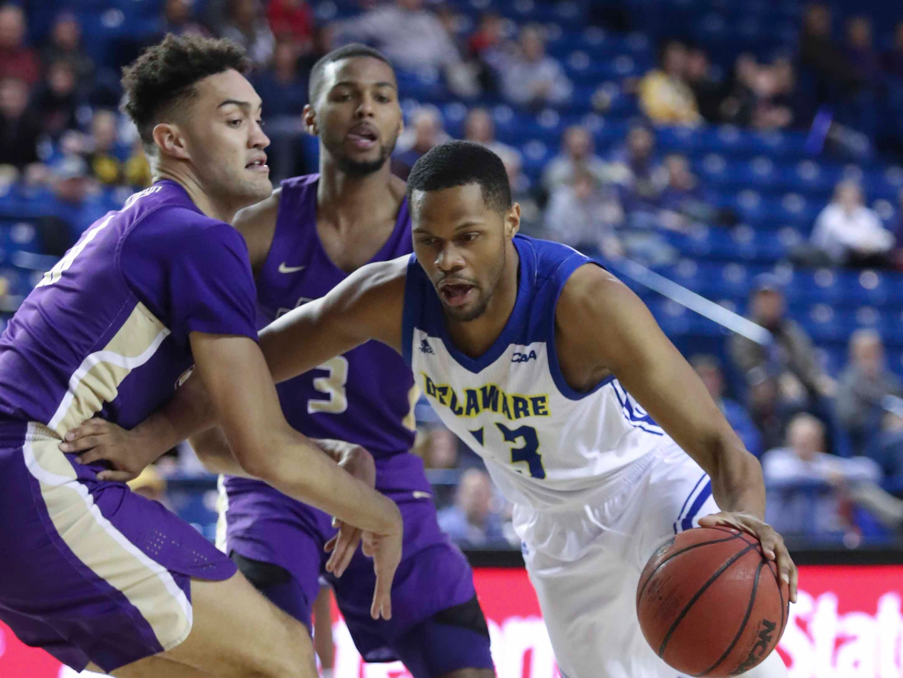 Delaware's Ryan Johnson (right) pushes to the basket against James Madison's Zach Jacobs (left) and Stuckey Mosley in the second half of the Blue Hens' 76-69 win at the Bob Carpenter Center Thursday.