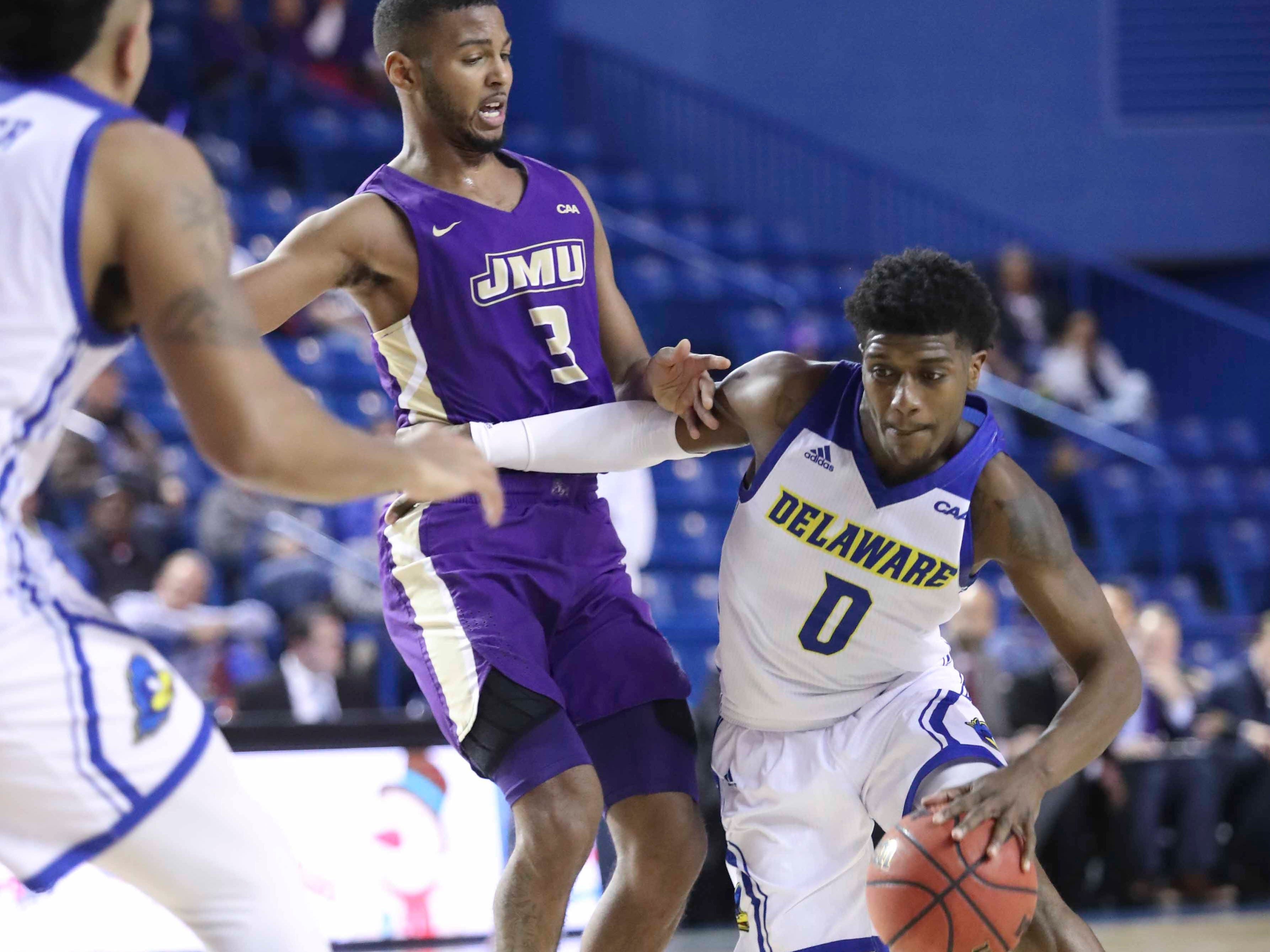 Delaware's Ryan Allen gets past James Madison's Stuckey Mosley in the second half of the Blue Hens' 76-69 win at the Bob Carpenter Center Thursday.