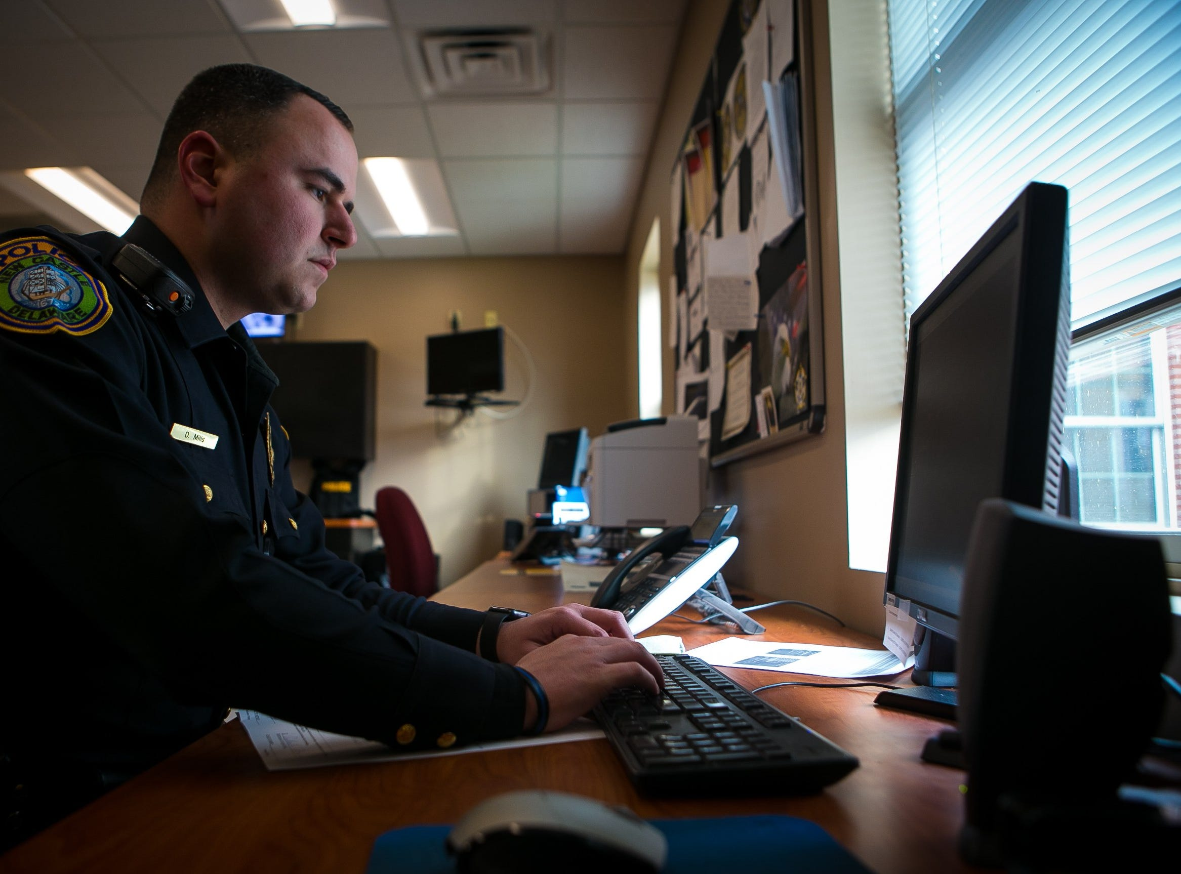 New Castle Police officer Dominick Mills, 23, does paper work on a case.