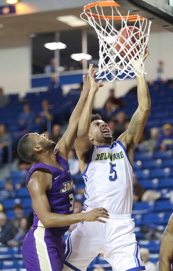 Delaware's Eric Carter gets two of his 26 points against James Madison's Stuckey Mosley in the first half at the Bob Carpenter Center Thursday.