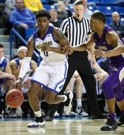 Delaware's Ryan Allen (0) drives against James Madison's Darius Banks in the second half of the Blue Hens' 76-69 win at the Bob Carpenter Center Thursday. Allen scored a career-high 29 points.