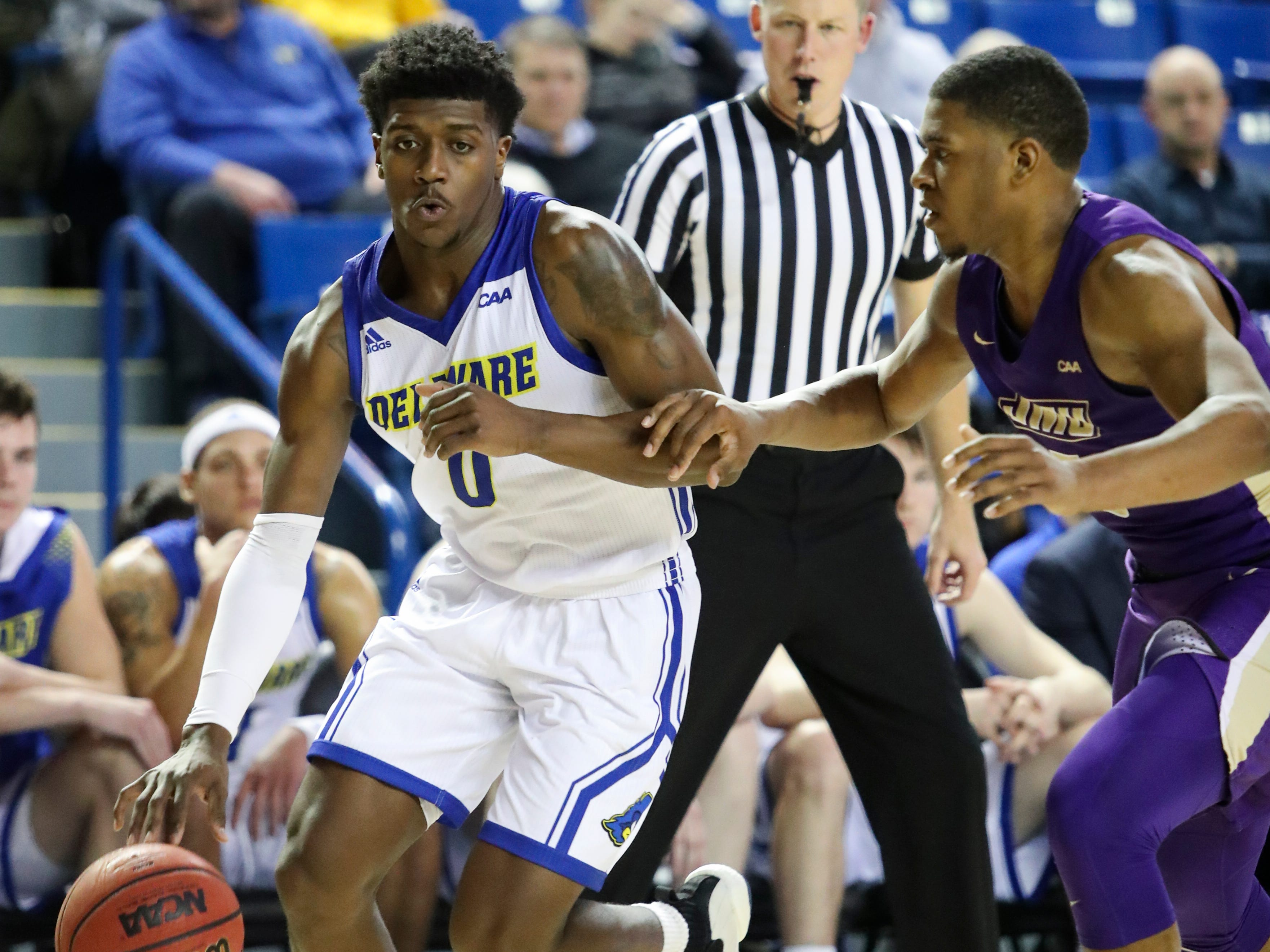 Delaware's Ryan Allen (0) drives against James Madison's Darius Banks in the second half of the Blue Hens' 76-69 win at the Bob Carpenter Center Thursday.