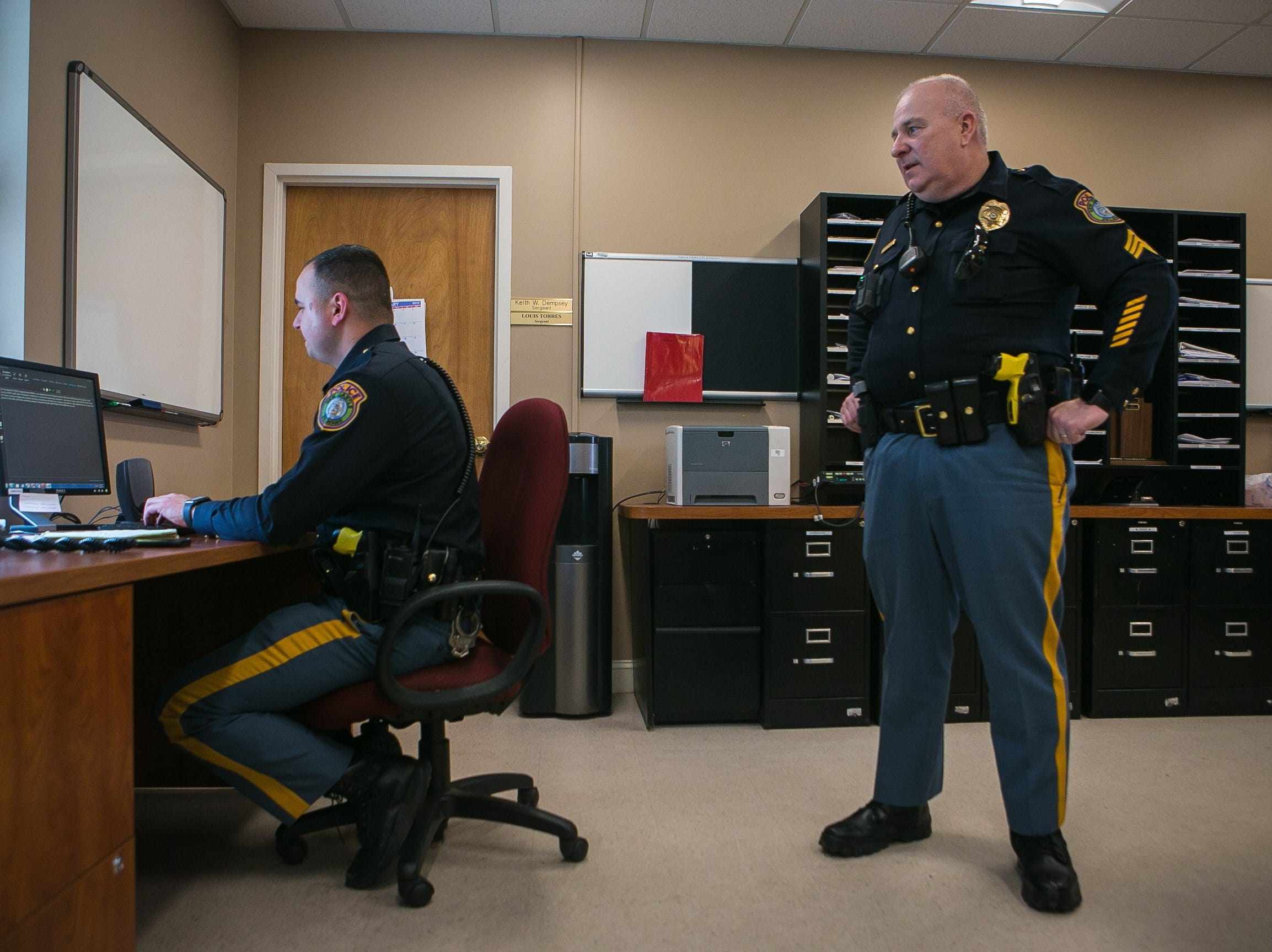 New Castle Police officer Dominick Mills, 23, prepares a warrant on a suspect as his supervisor Sgt. Keith Dempsey looks on.