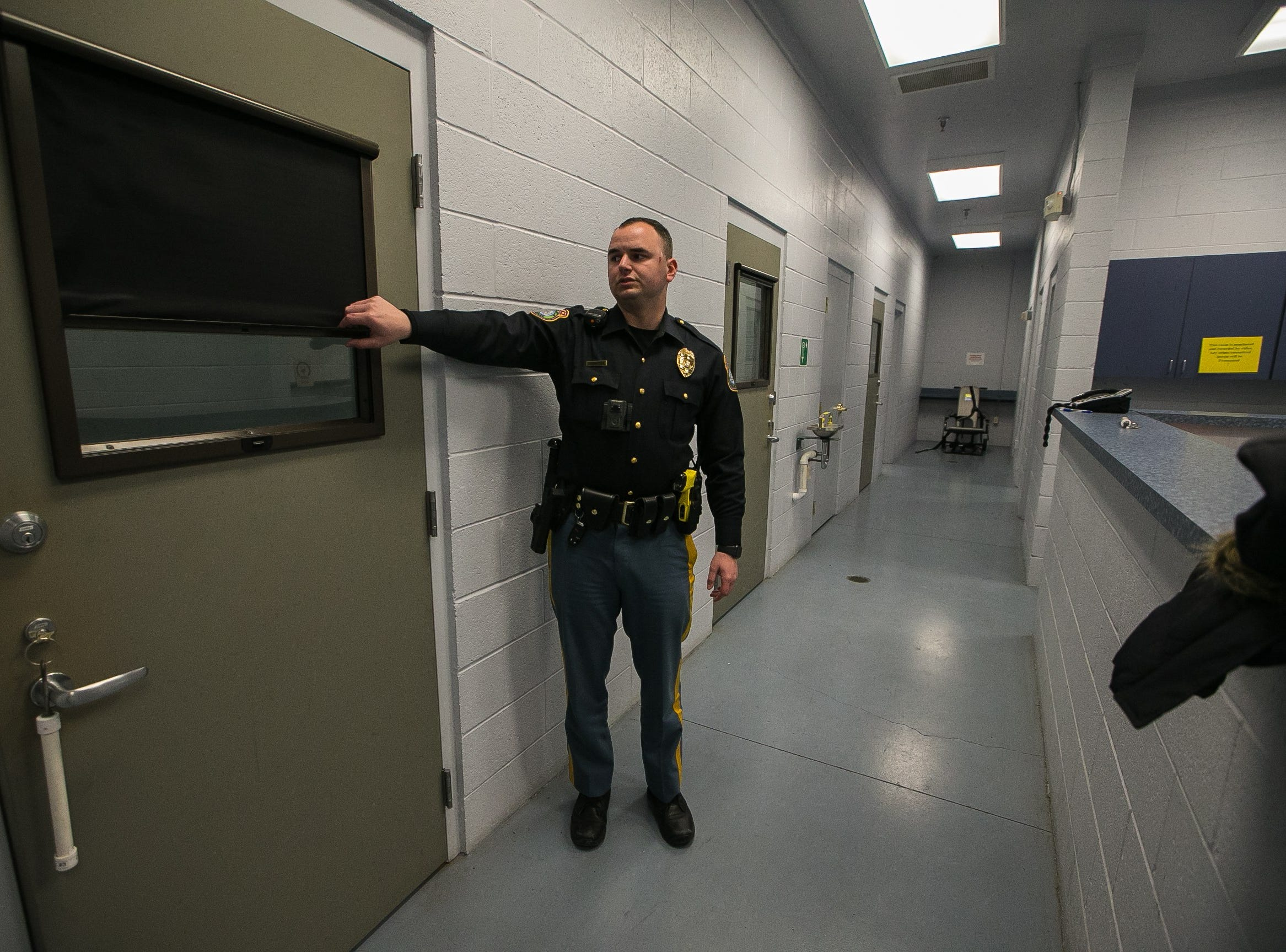 New Castle Police officer Dominick Mills, 23, shows where people are precessed at the city's police station.