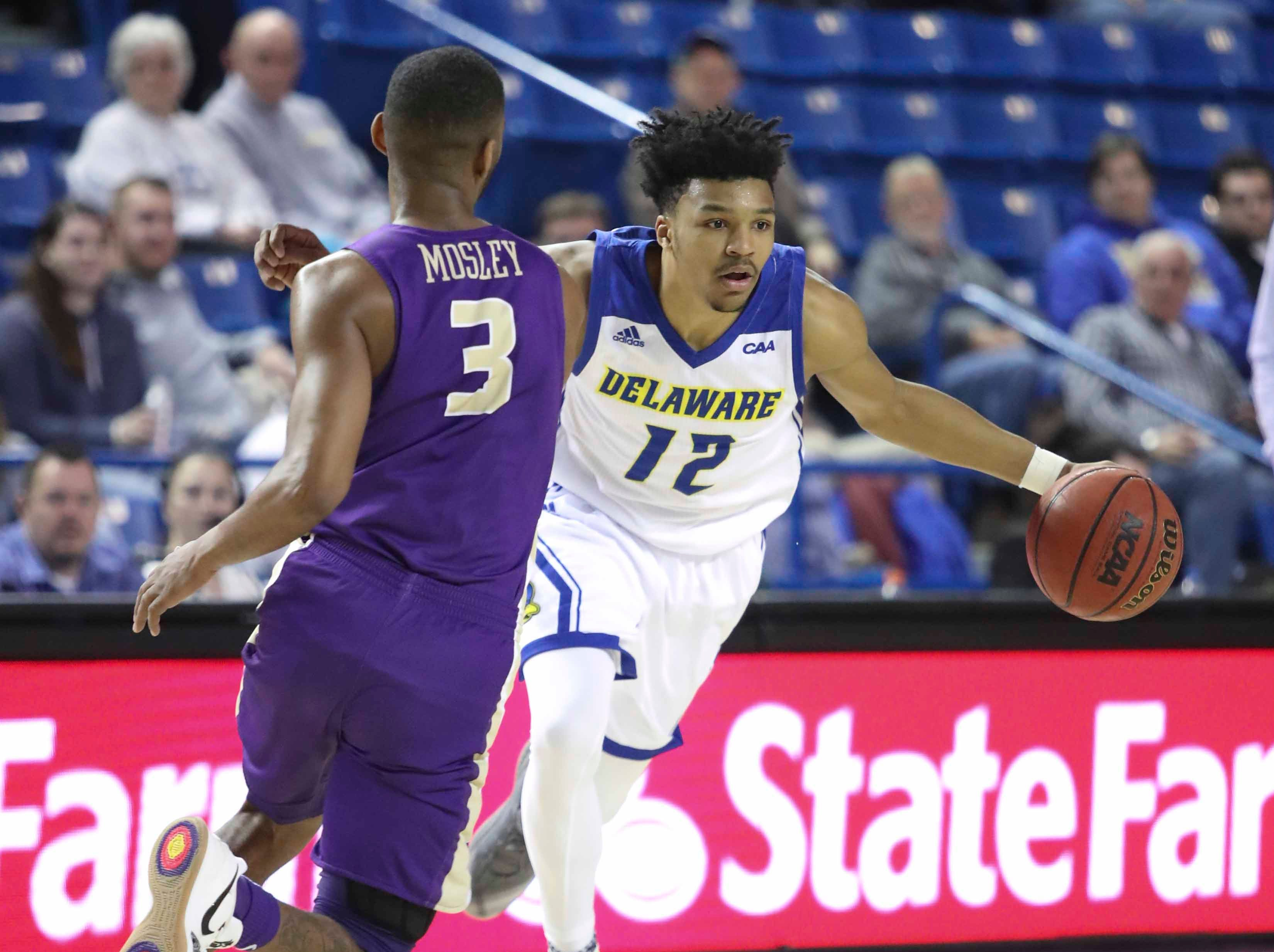 Delaware's Ithiel Horton dribbles against James Madison's Stuckey Mosley in the second half of the Blue Hens' 76-69 win at the Bob Carpenter Center Thursday.