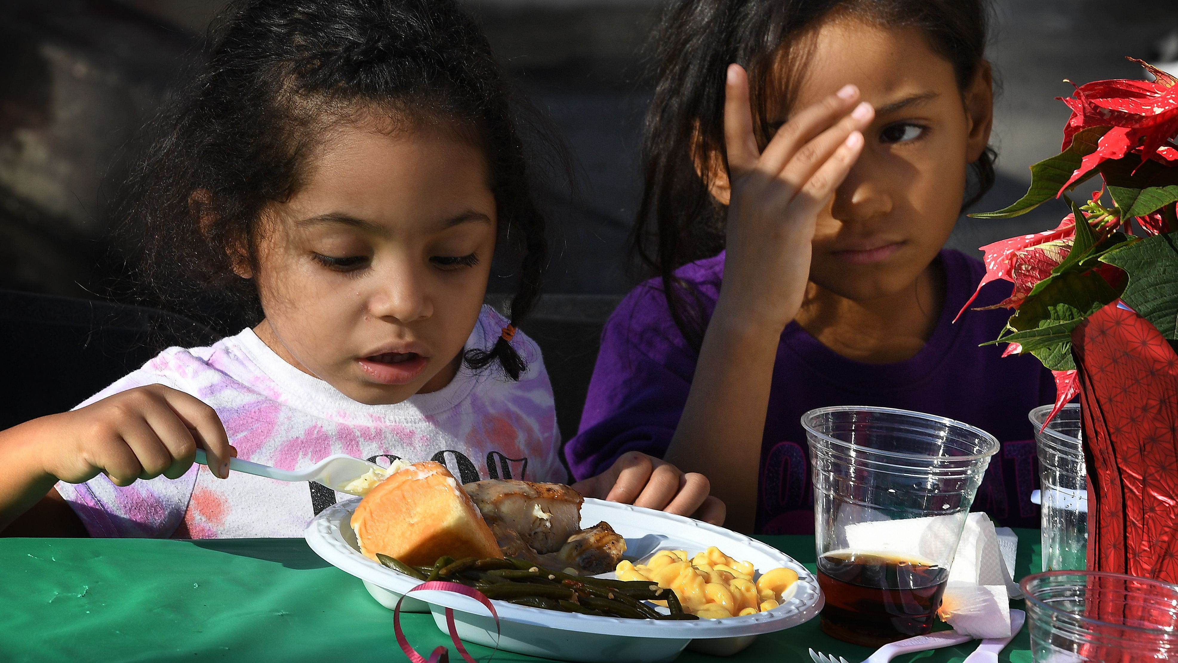 Children are among the desperately poor homeless who live on Los Angeles' Skid Row, which have been hurt by the teachers' strike. Here are two enjoying a meal last month at a holiday feast event.