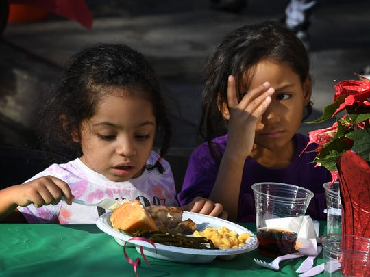 Children are among the desperately poor homeless who live on Los Angeles' Skid Row. They've been hurt by the teachers strike. Here are two enjoying a meal last month at a holiday feast event.