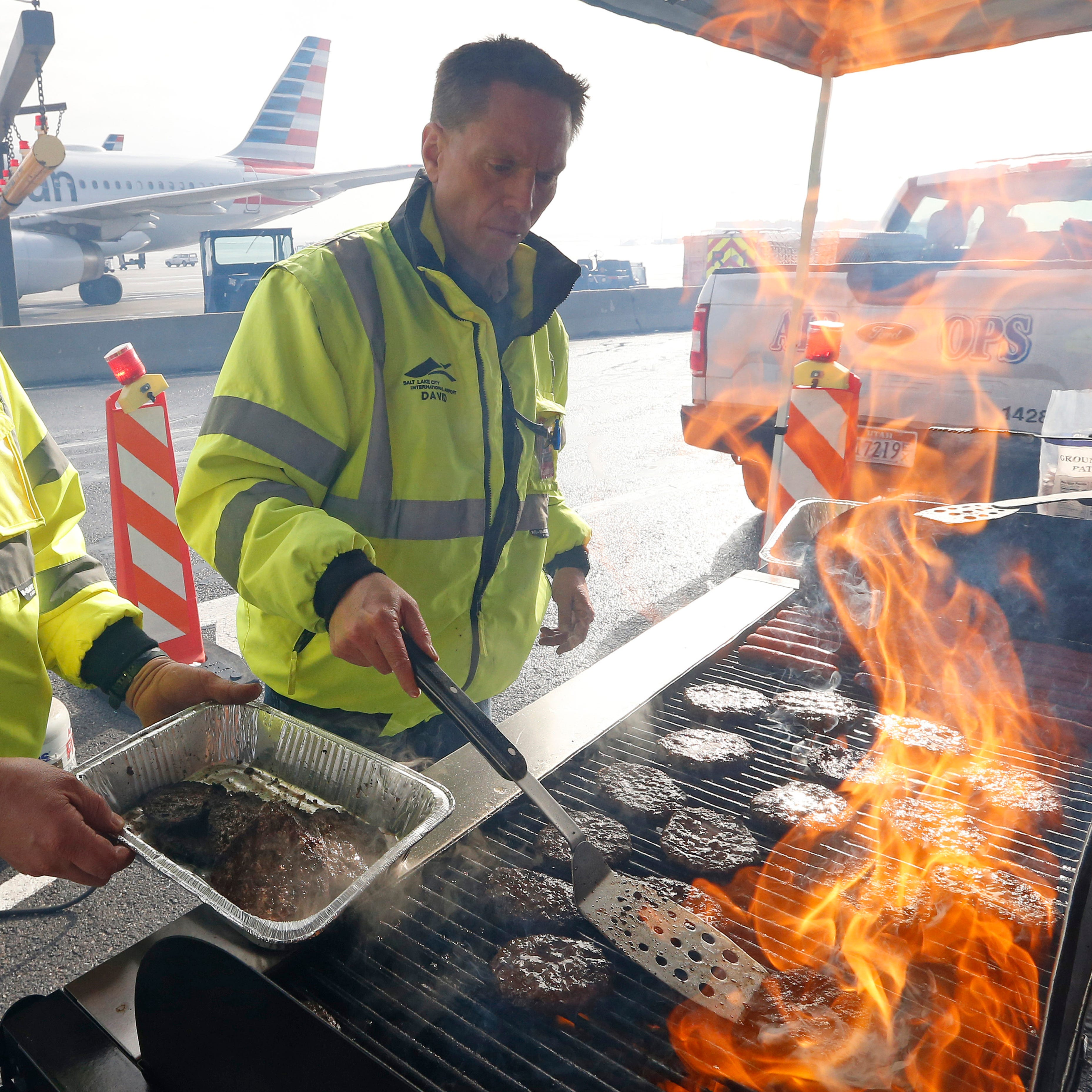 Airport operation workers wearing fluorescent safety jackets flipped burgers and hot dogs on a grill set up on a tarmac in front of a plane at Salt Lake City International Airport, Wednesday, Jan. 16, 2019, in Salt Lake City. In Salt Lake City, airport officials treated workers from the TSA, FAA and Customs and Border Protection to a free barbecue lunch as a gesture to keep their spirits up during a difficult time. (AP Photo/Rick Bowmer) ORG XMIT: UTRB101
