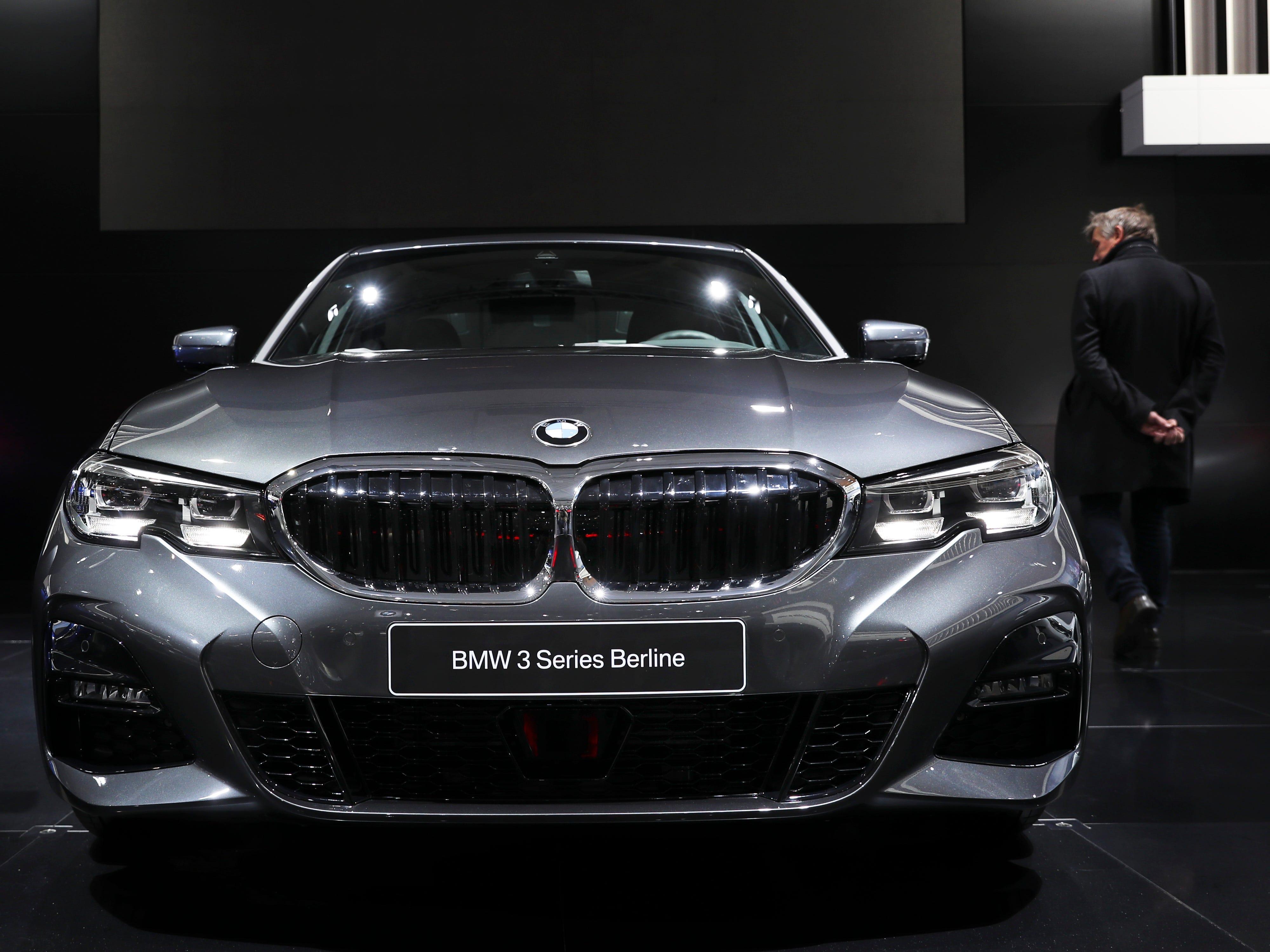 A man walks next to the new BMW 3.