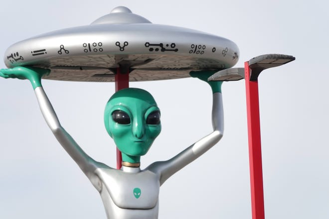 An alien greets tourists and invites them to buy jerky, candy and T-shirts in Baker, California.