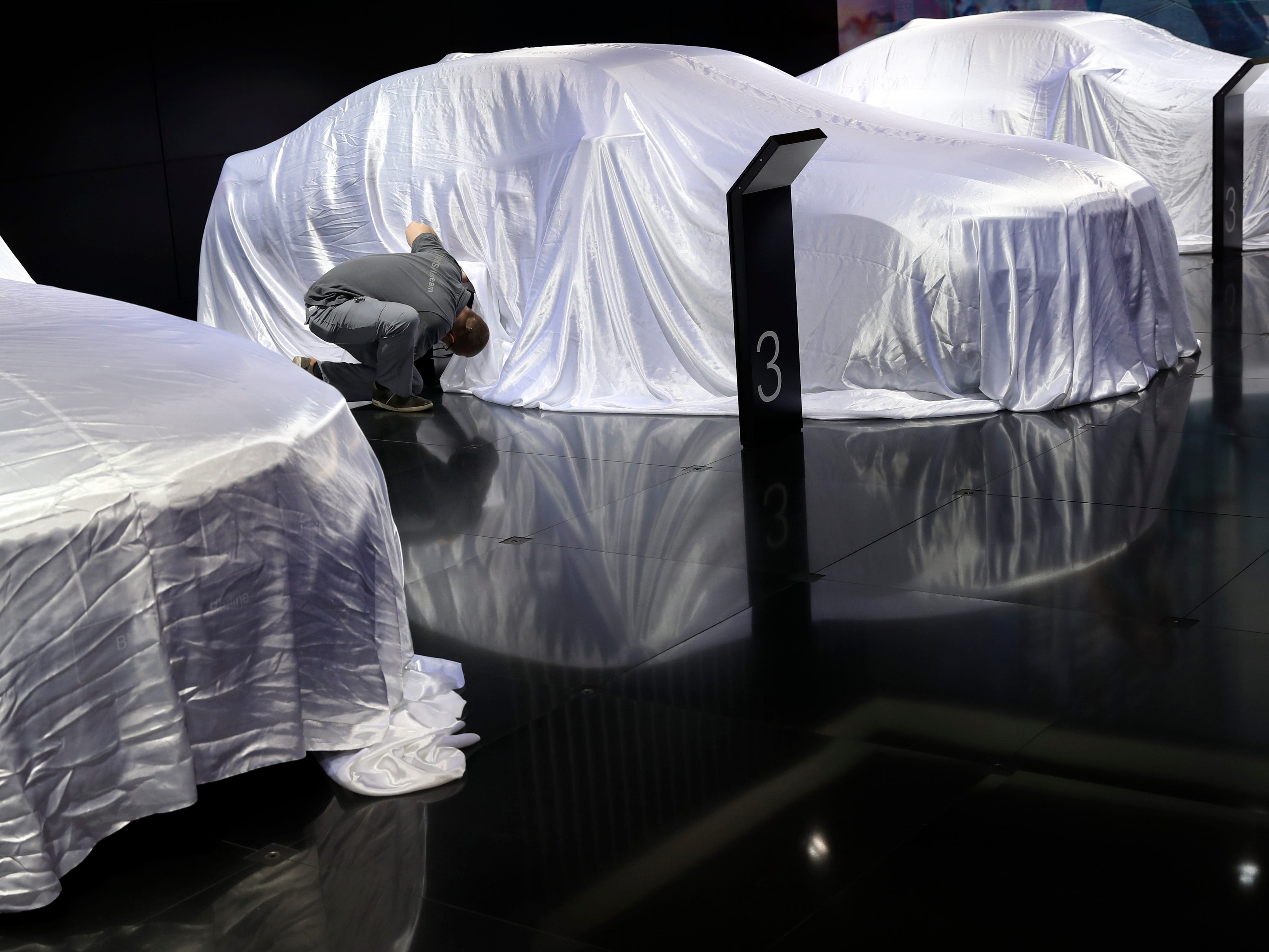 An employee looks under a new BMW 3 before its unveiling.