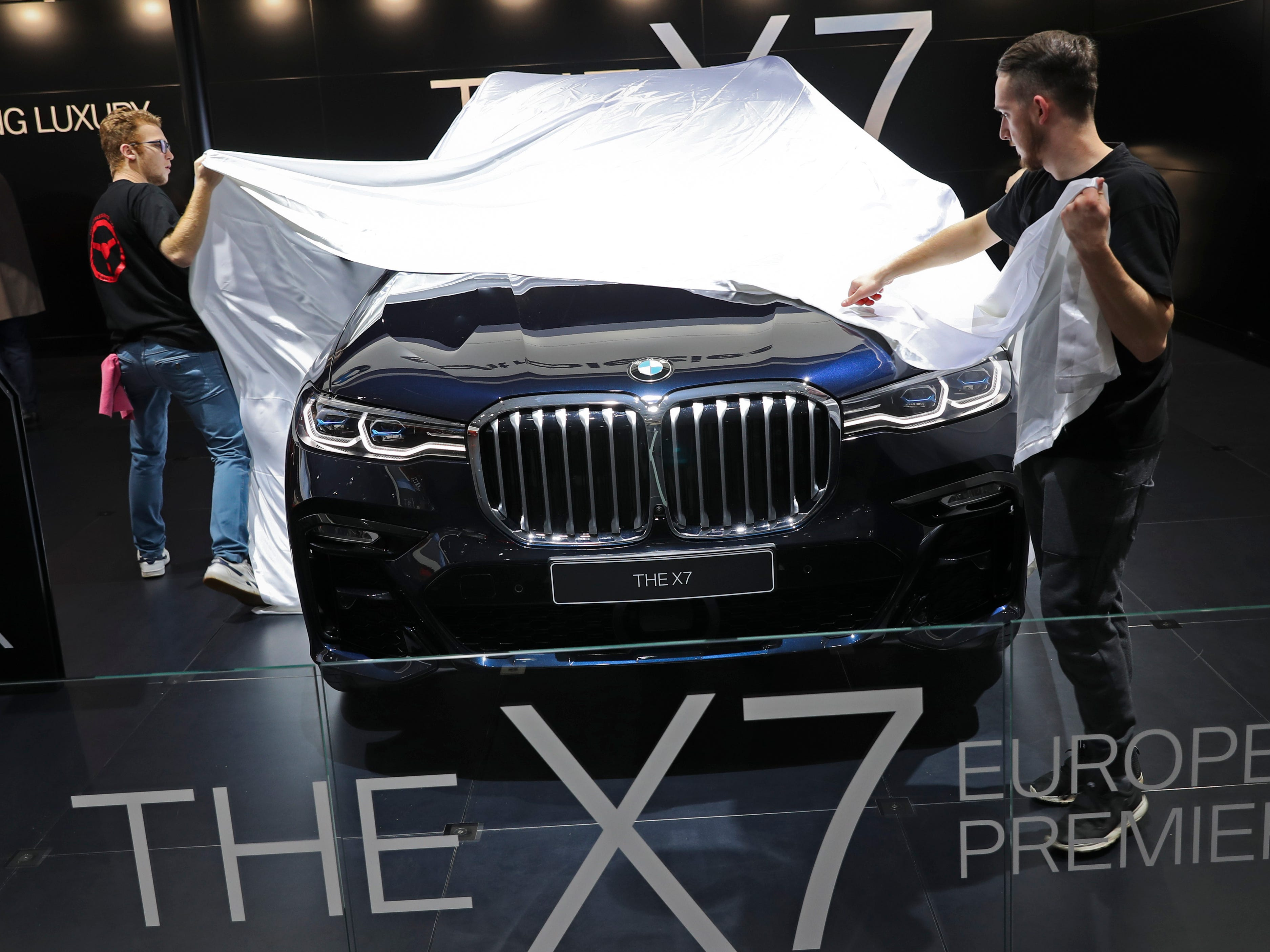 Employees cover the new BMW X7 before its unveiling.