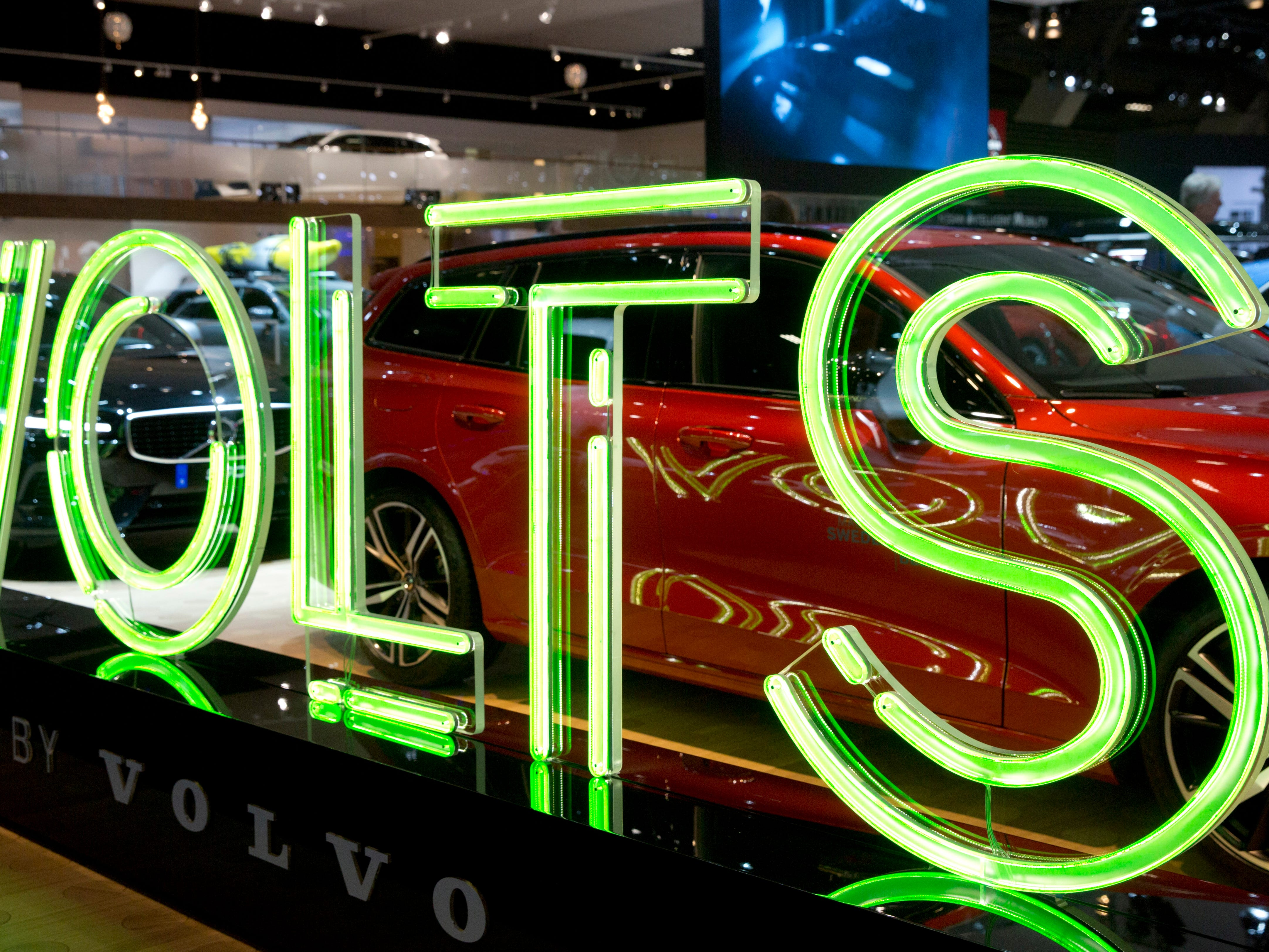 A neon sign which reads volts at the Volvo car stand.