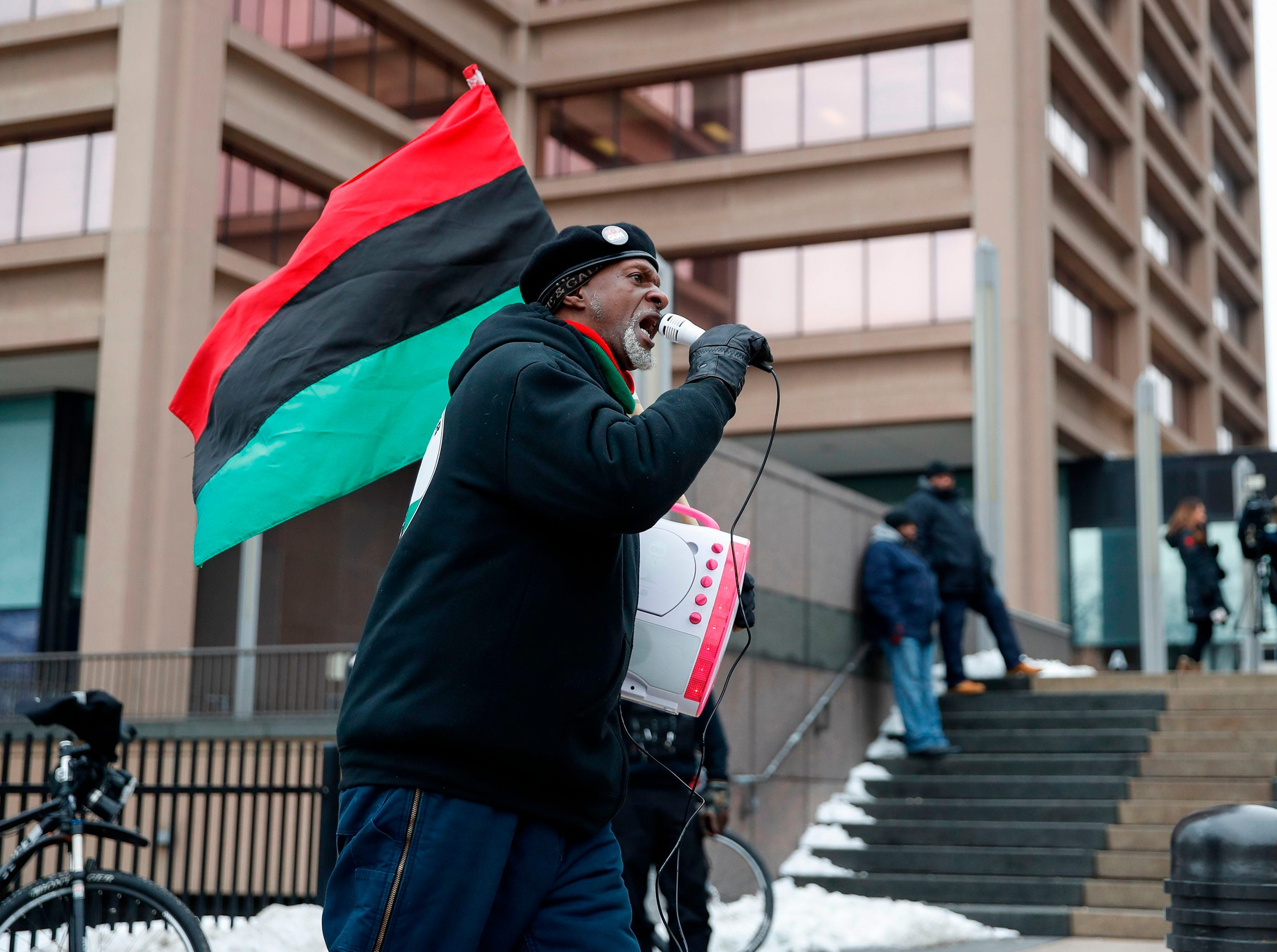 A man, with a Pan-African flag, protests outside of the Leighton Criminal Courts Building during the sentencing of Officer Jason Van Dyke on Jan. 18, 2019 in Chicago, Illinois.