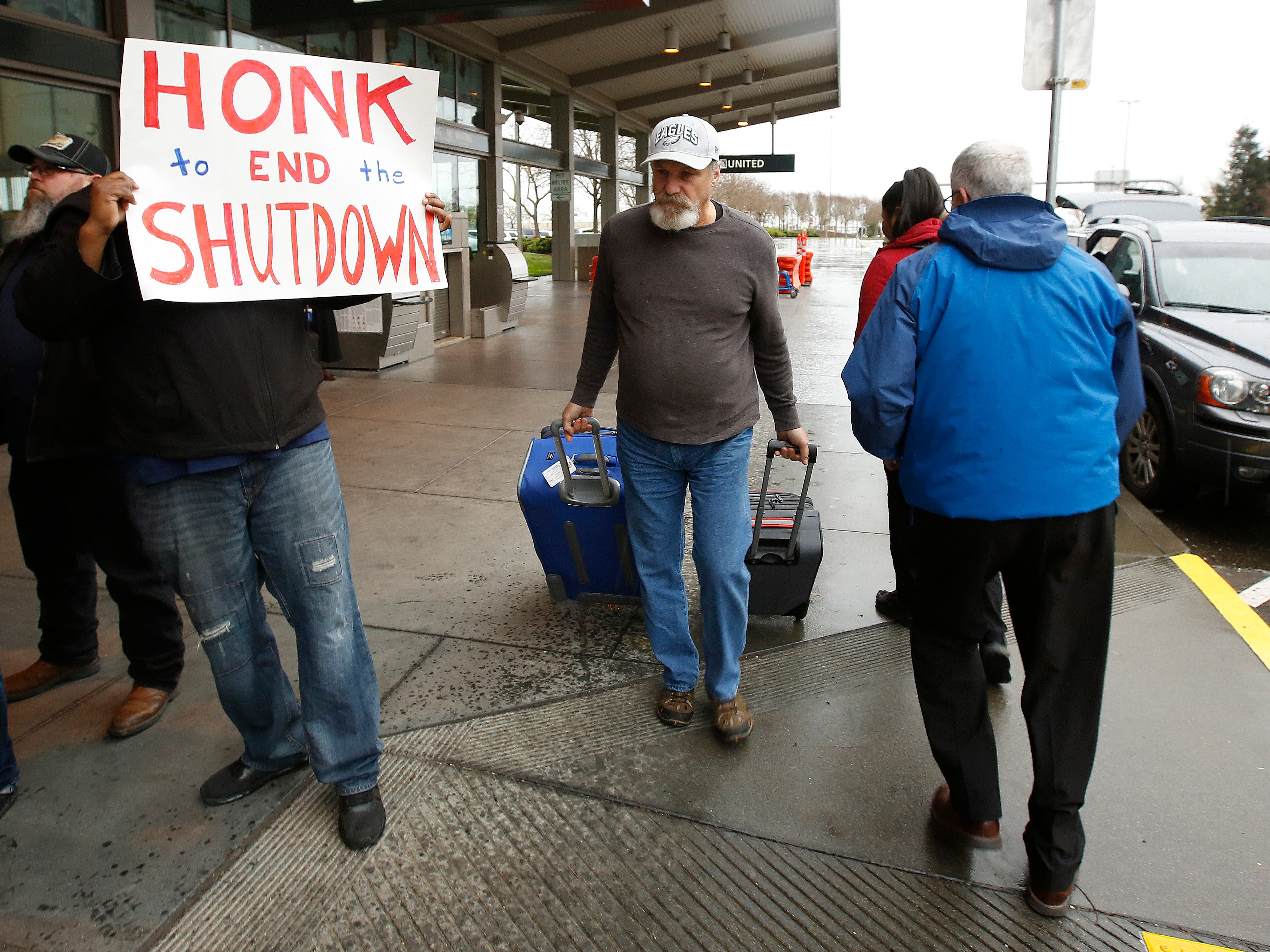 A man heading into the Sacramento International Airport passes demonstrators calling for President Donald Trump and Washington lawmakers to end the shutdown, Wednesday, Jan. 16, 2019, in Sacramento, Calif. More than two dozen federal employees and supporters called for an end to the partial government shutdown now in its fourth week. (AP Photo/Rich Pedroncelli) ORG XMIT: CARP302