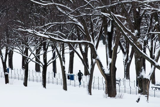 A jogger runs on a snow-covered path near the Lincoln Memorial Reflecting Pool in Washington, DC, o January 14,2019, in the first round of winter weather this season. Two blasts of cold air from Canada are expected to produce near-blizzard conditions in parts of the northeast and plummeting temperatures through the weekend.