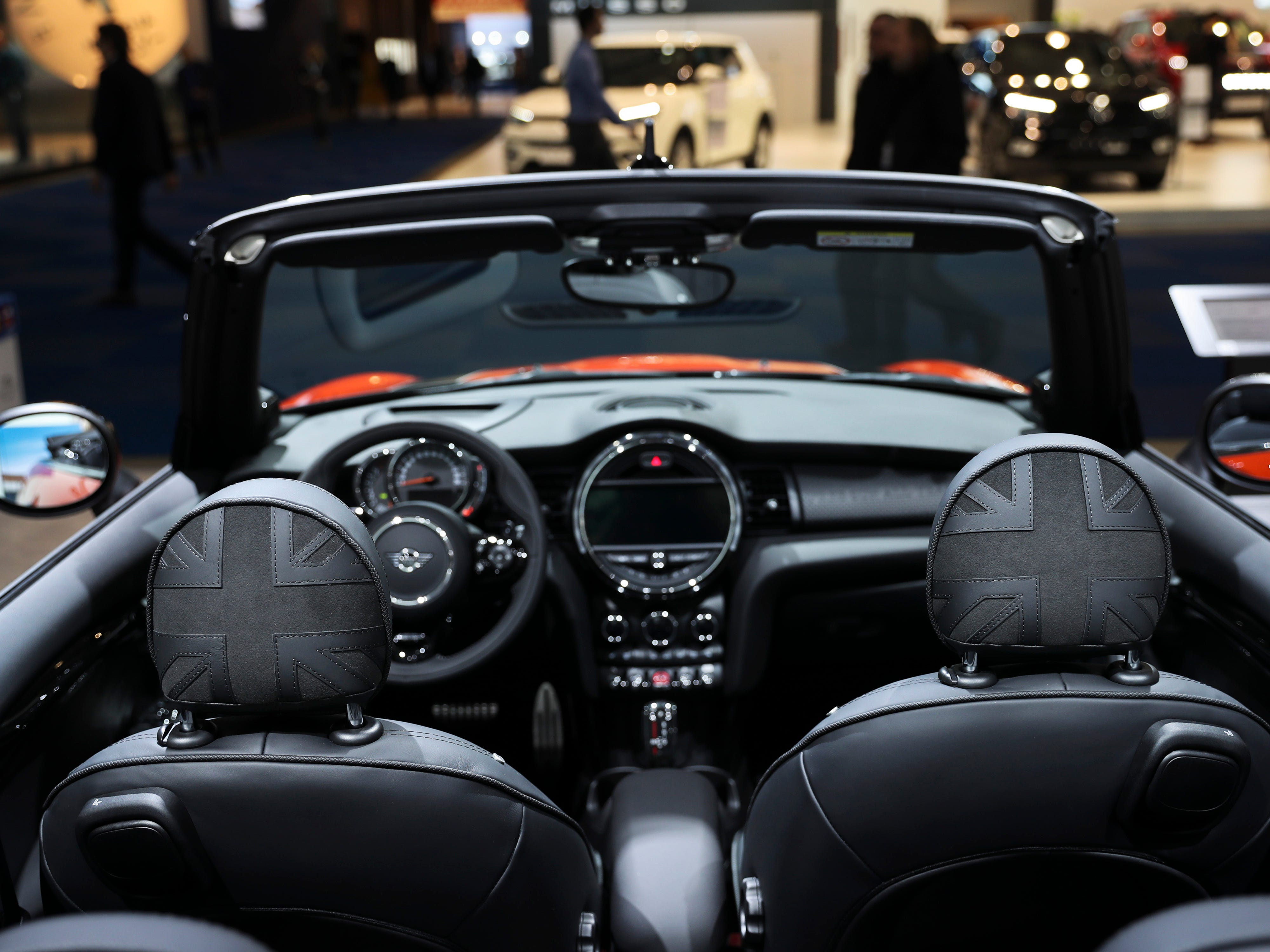 People walk past the new Mini Cabrio on display at the Brussels Auto Show. The show runs through Jan. 27, 2019.