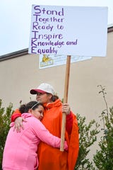 Second grade teacher Rosa Rubalcava hugs her daughter Alina Ramirez as she stands on the picket line at Telfair Elementary School. Alina is a student at the school.