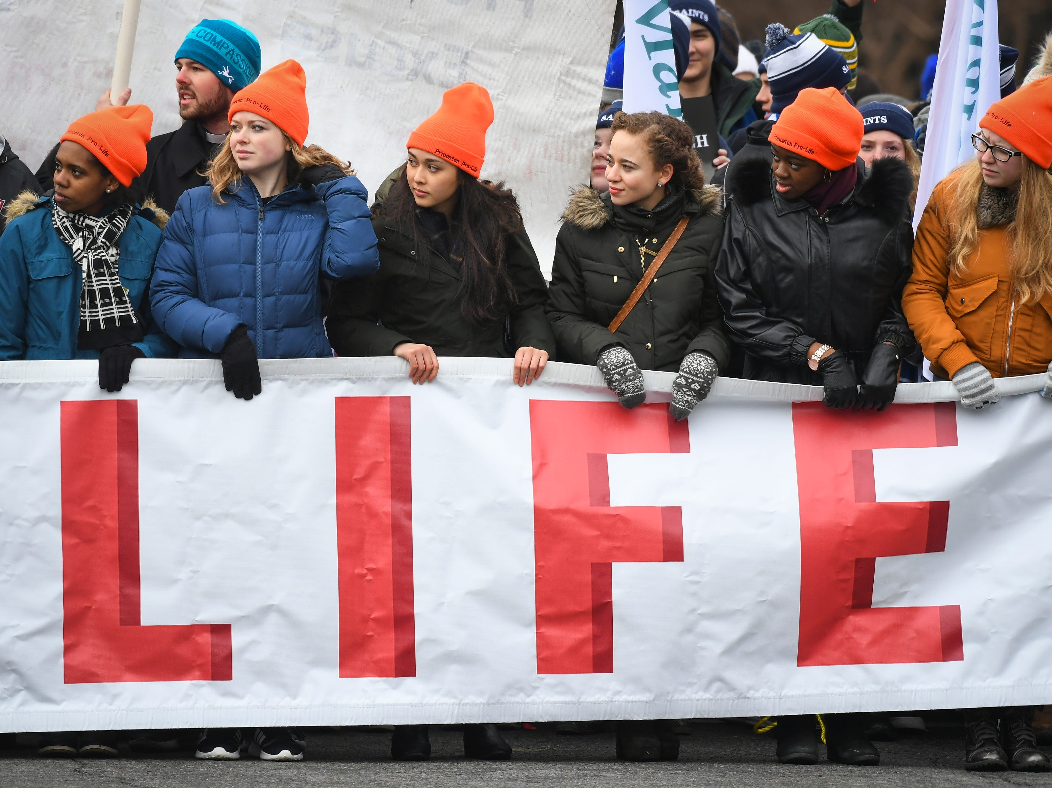 """Signs reading """"Choose love, Choose life,"""" """"I am the pro-life generation,"""" and """"Defund Planned Parenthood"""" dotted the crowd gathering under hazy, wintry skies at the morning rally."""