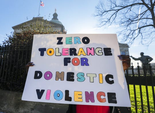 A woman holds a protest sign reading 'Zero Tolerance for Domestic Violence' during an anti-domestic violence rally outside the Georgia State Capitol in Atlanta, Georgia, on Feb. 8, 2018.