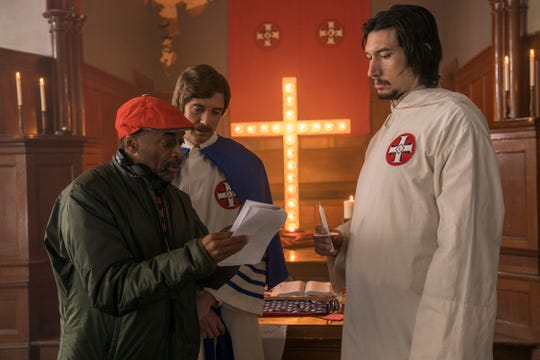 "Spike Lee, left, goes over a scene with Topher Grace and Adam Driver on the set of ""BlacKkKlansman."""