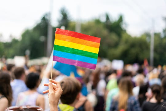 Gay rainbow flag at  gay pride parade with blurred participants in the background