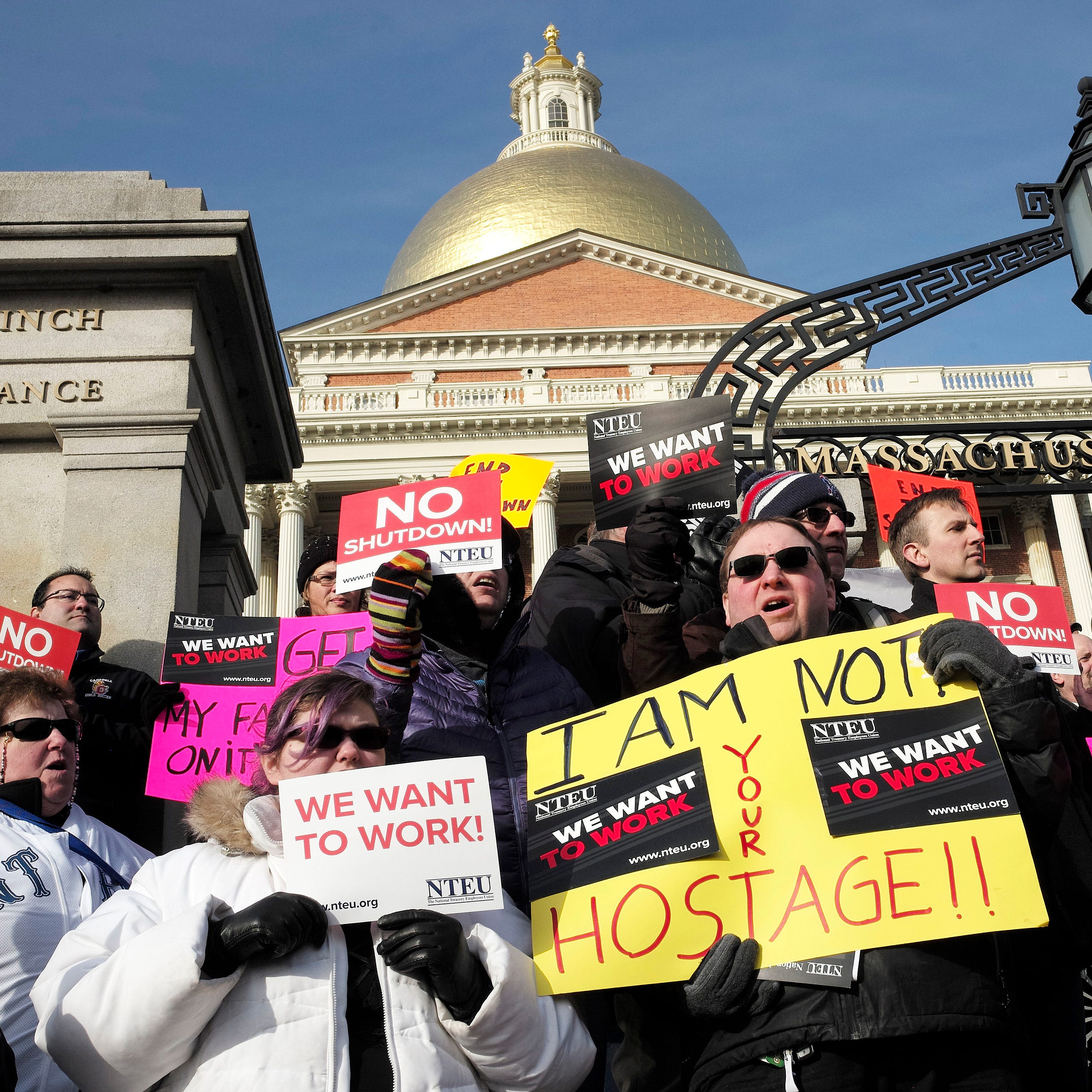 Federal employees are pictured protesting the government shutdown in front of the Statehouse in Boston.