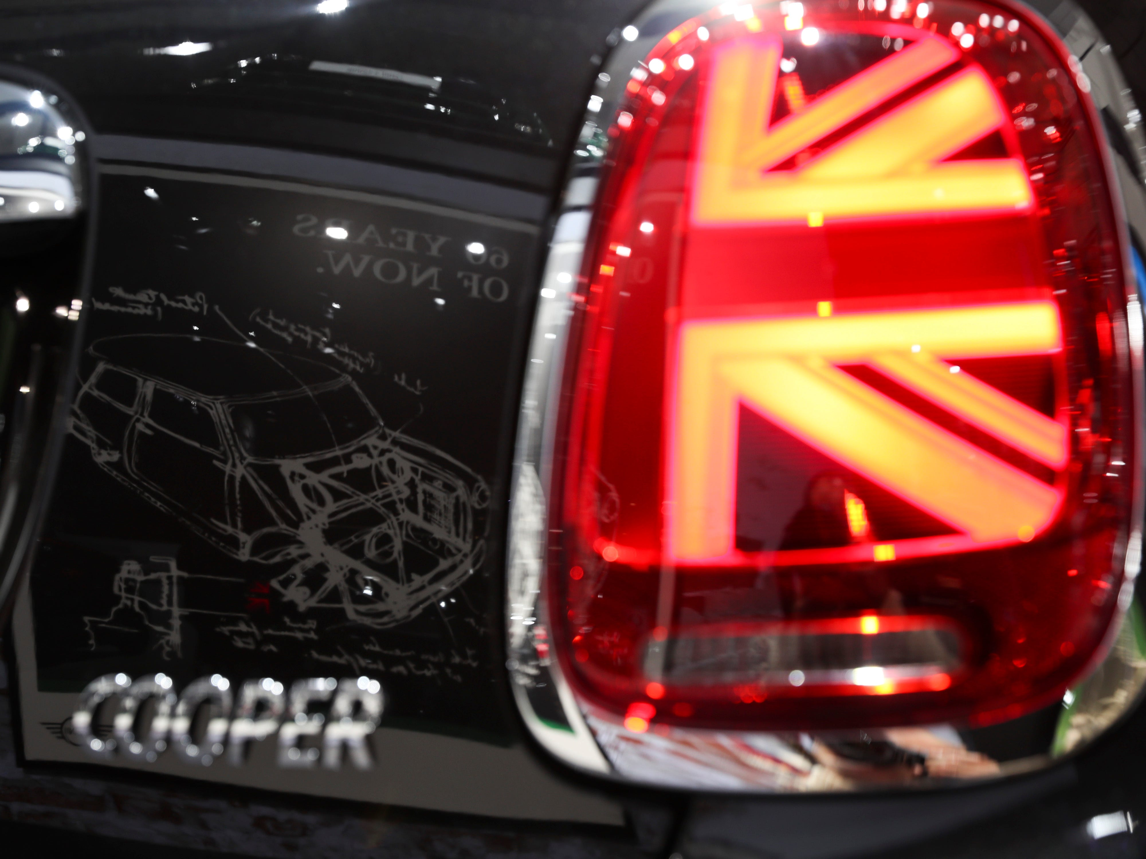A Mini car sketch is reflected on the new Mini Cooper.