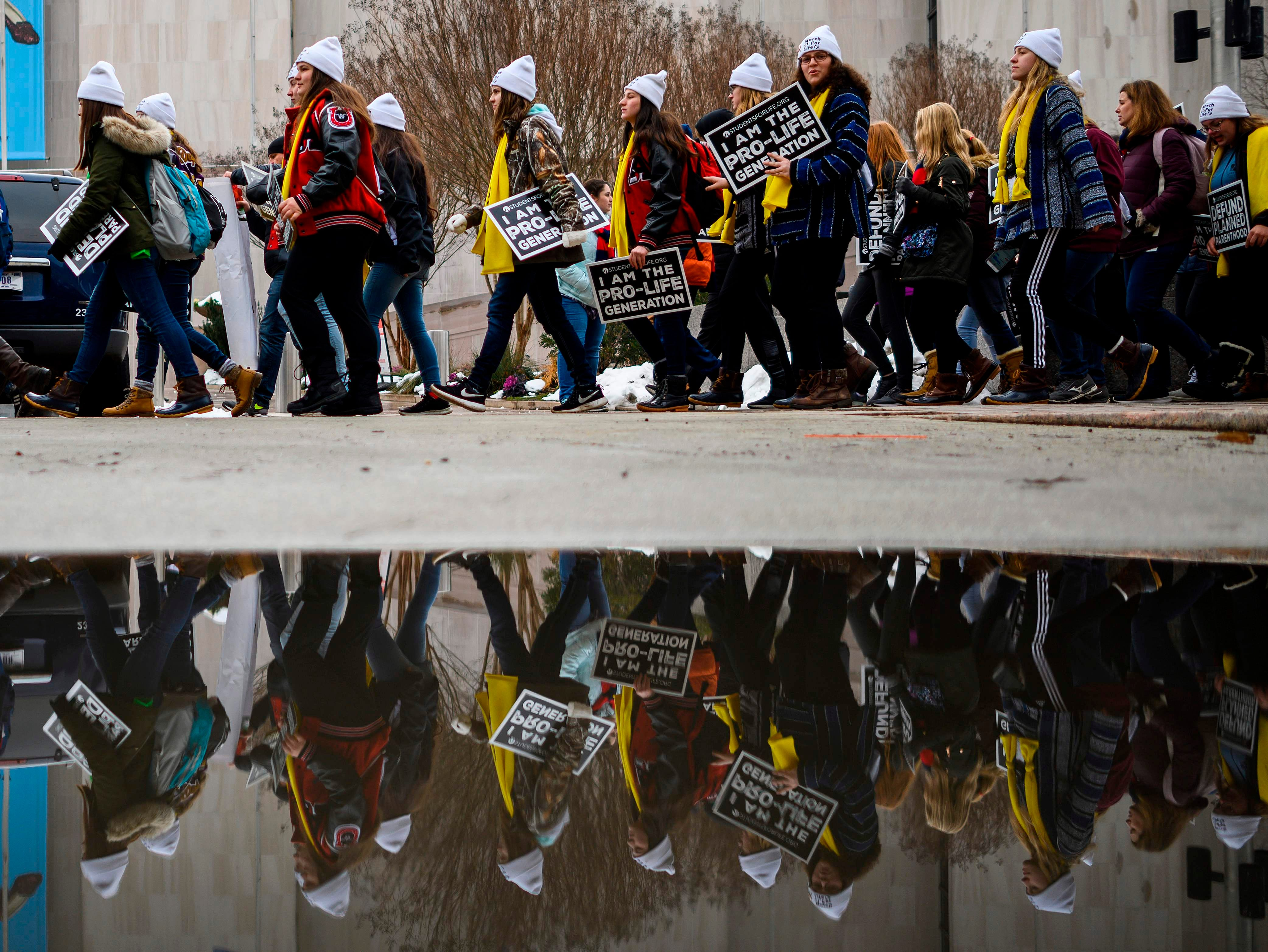 Students and activists carry signs during the annual March for Life in Washington, DC on Jan. 18, 2019.