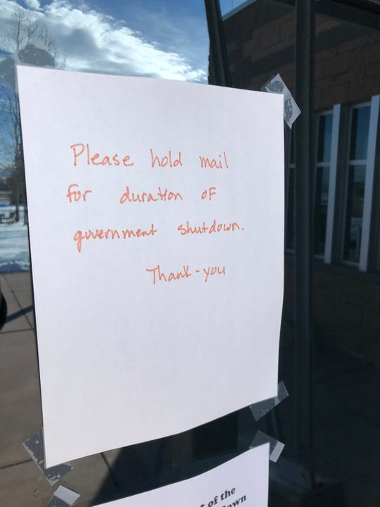 Faded red lettering asks delivery drivers to hold mail and packages during the federal government shutdown. The sign is posted on the front of the Bureau of Land Management offices in Craig, Colorado, a small coal-mining town near the Wyoming border.