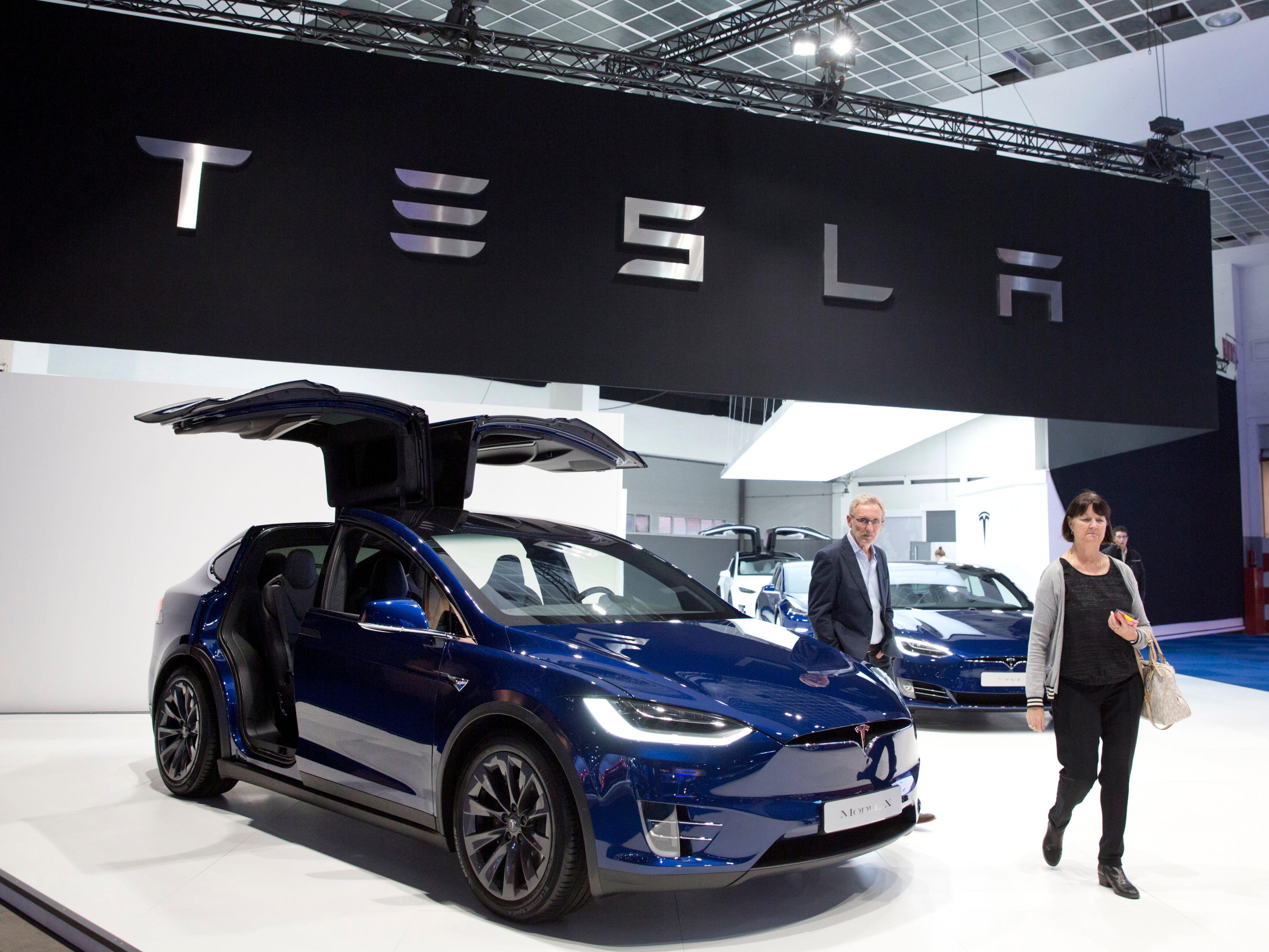 A couple walk next to the new Tesla Model X.