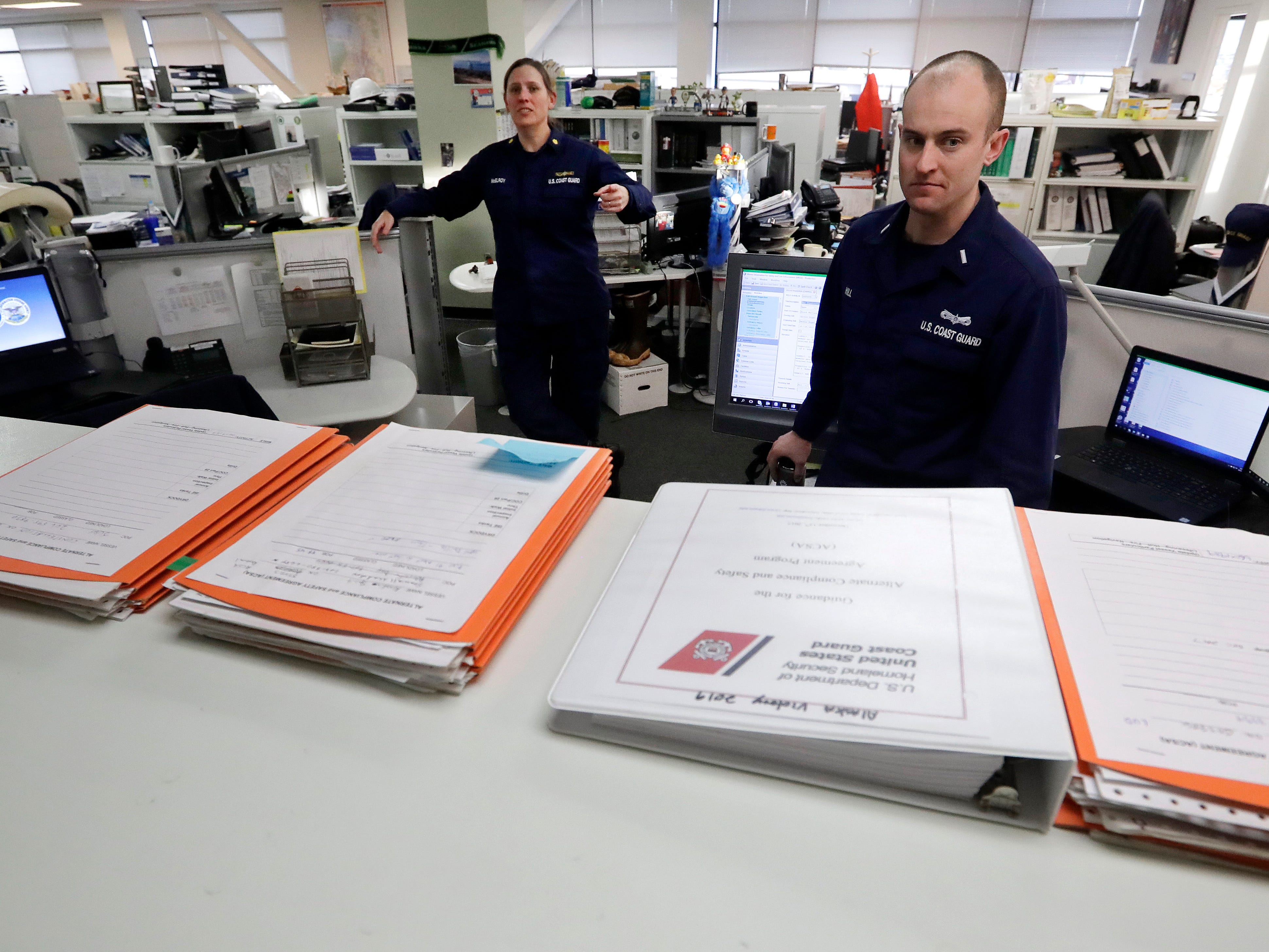 U.S. Coast Guard Lt. Cmdr. Amy McElroy, left, and Lt. j.g. Sean Hill, who both missed a paycheck a day earlier during the partial government shutdown, talk about the stacks of fishing fleet inspections backing-up in the marine inspection office at Sector Puget Sound base Wednesday, Jan. 16, 2019, in Seattle. The four civilian employees who normally handle the paperwork have been furloughed, leaving it to Hill to complete, along with his other duties. The Coast Guard is part of the U.S. Department of Homeland Security, which is unfunded during the shutdown, now in its fourth week. (AP Photo/Elaine Thompson) ORG XMIT: WAET108