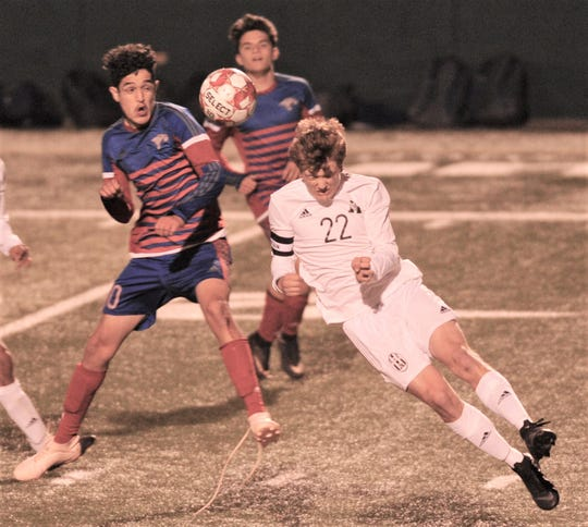 Abilene High's Colton Wilson (22) leaps for a header while battling a Cooper player for the ball. The teams played to a 2-2 tie in the nondistrict boys soccer game Friday, Jan. 18, 2019, at Shotwell Stadium.
