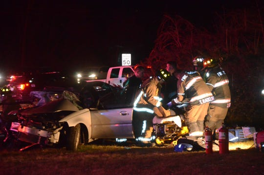 First responders remove one of the women from the wreckage Friday night. Three women were injured after fleeing from police, officials said.