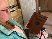 Kim Bullman shows off a journal owned by her great-aunt Viola. The journal, along with several letters and photo negatives, was found under a floorboard in the attic of a Bremerton home.