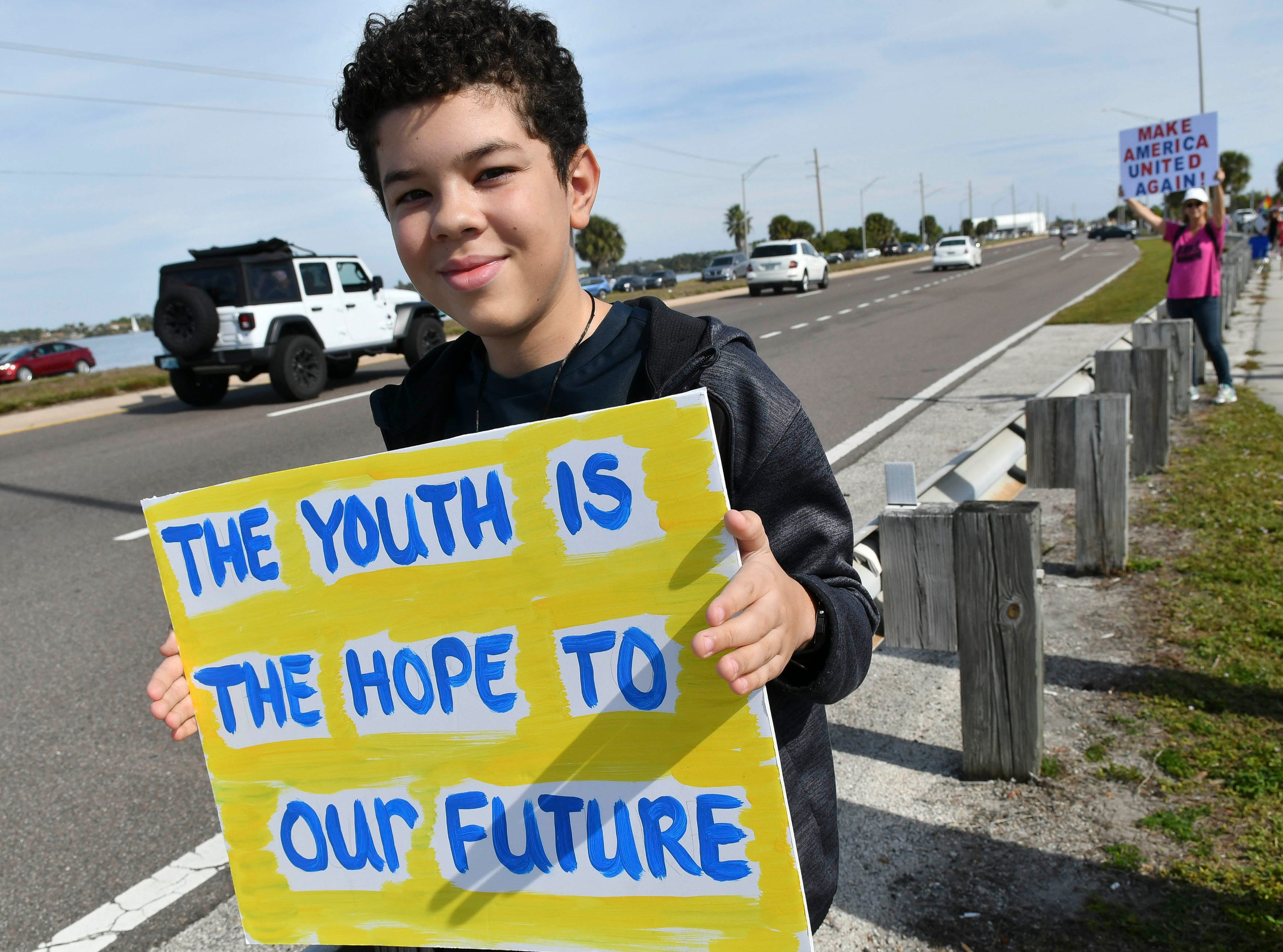Isaiyah Llauger holds his sign along the Eau Gallie Causeway Saturday. Hundreds of people walked the causeway in Melbourne during a local observance of the national Women's March.