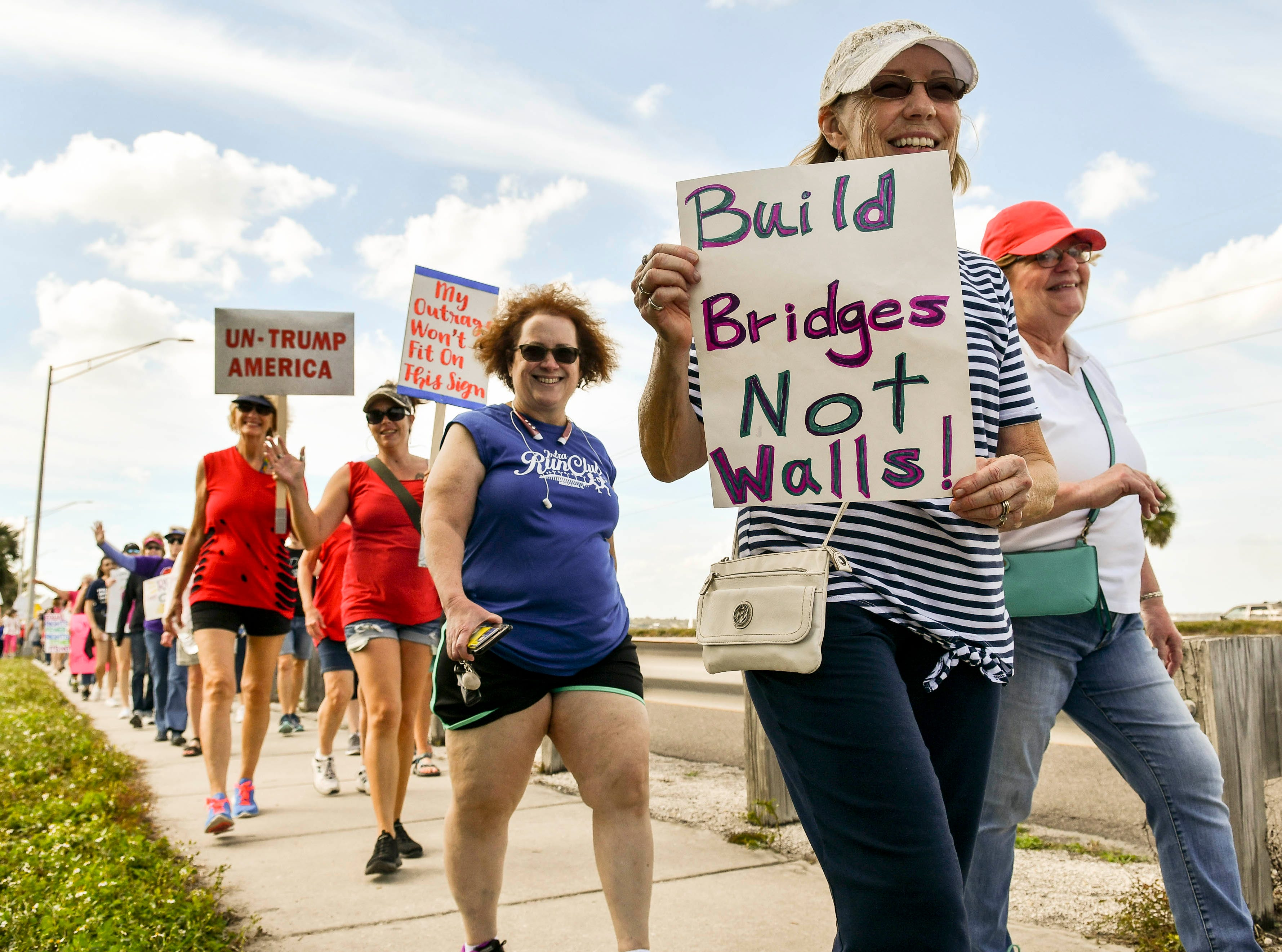 Hundreds of people walk the Eau Gallie Causeway in Melbourne during a local observance of the national Women's March.