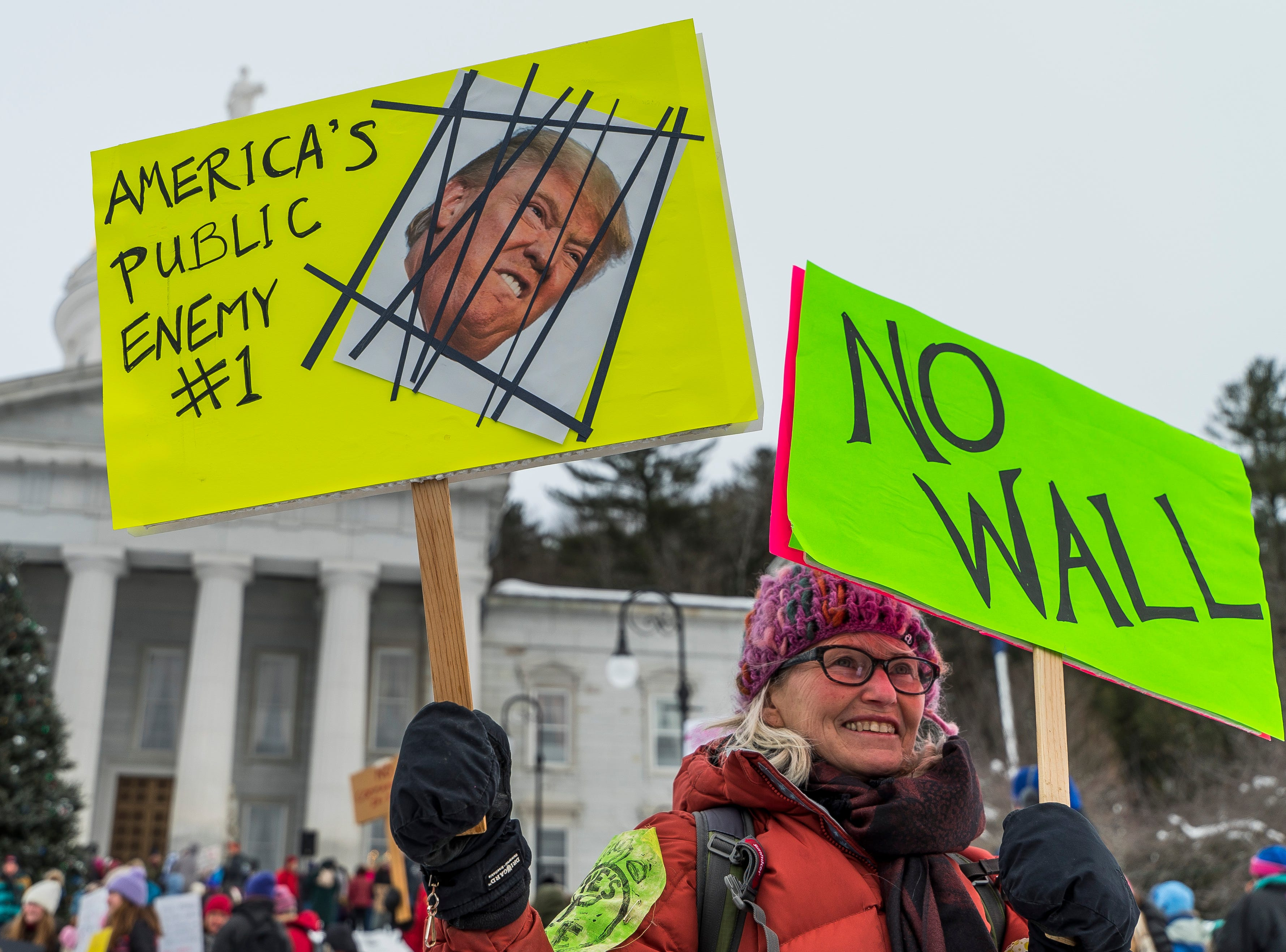 Susan Murry-Grage of Underhill, Vt., holds up anti-Tump signs at the Women's March Vermont rally in Montpelier on Saturday, Jan. 19, 2019. According to police, about 700 to 1000 people attended the rally.