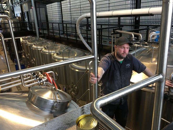 Jim Conroy checks the gauges before adding hop extract to a batch of Ouroboros beer at The Alchemist brewery in Stowe on Thursday, Jan. 17, 2019.