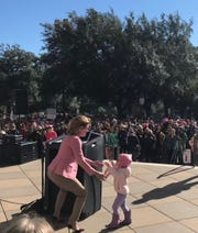 Wendy Davis, the unsuccessful 2014 Democratic nominee for Texas governor, is interrupted by her 2-year-old granddaughter, Ellis, while making a speech at the women's rally at the Texas Capitol in Austin, Jan. 19, 2019.