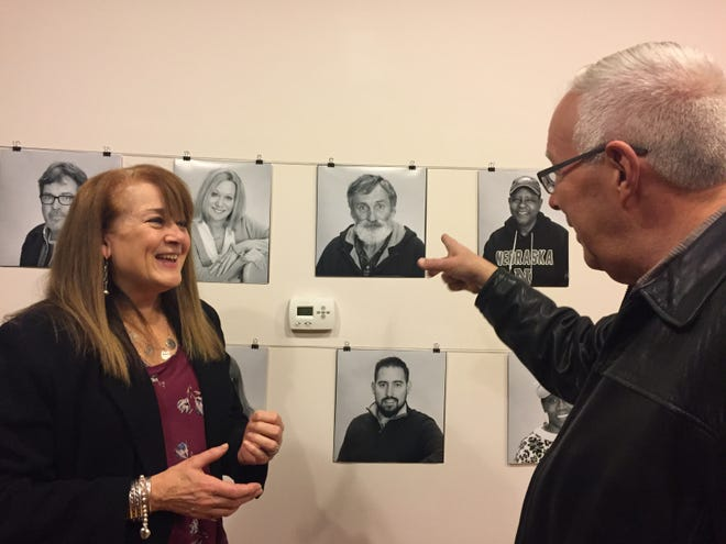 """Burlington City activist Harry Heck shares local stories with Nancy  Collier, secretary of the city-based New Jersey Arts Guild, at the opening of the """"Many Faces of Burlington"""" exhibit by photographer Michael Donahue. heck;s photo is in exhibit, which is being  hosted by The Dime, a new city art business leasing studio and gallery space to working artists."""