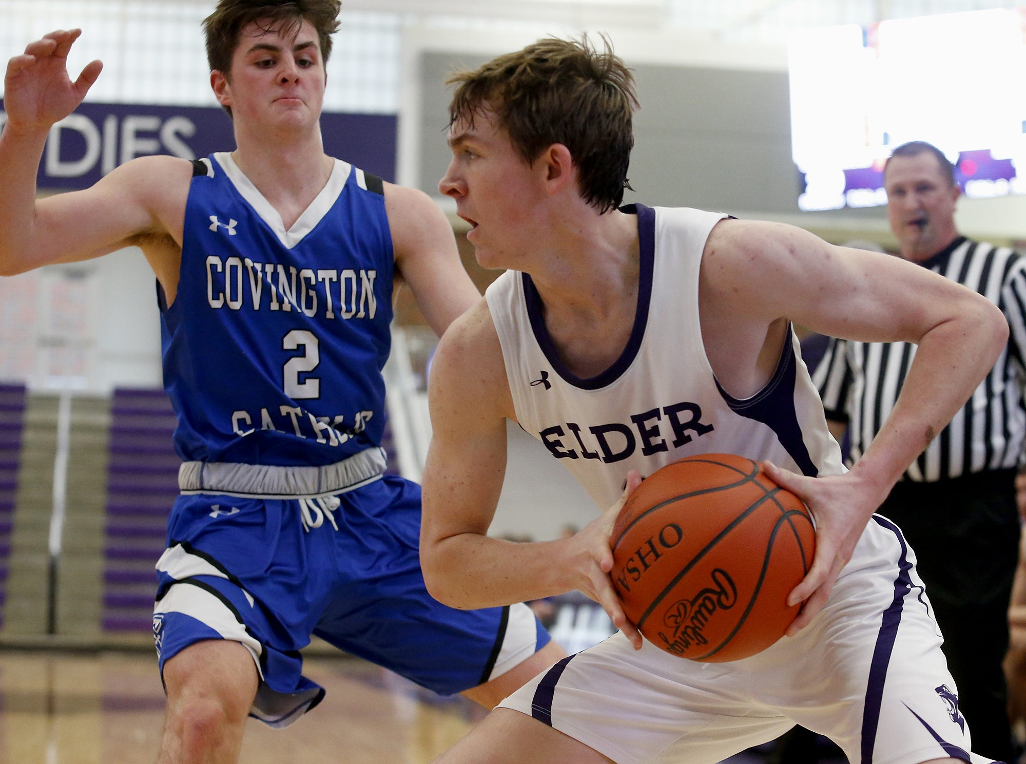 Elder guard Aidan Byrne looks for a teammate while covered by Covington Catholic guard Grant Disken during the Midwest King Classic at Jerry Lucas Court in Wade E. Miller Arena in Middletown Saturday, Jan. 19, 2019.