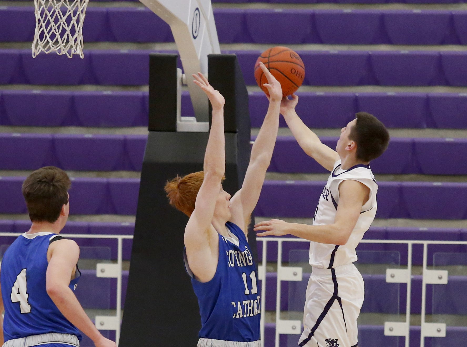 Elder guard Willard Cluxton puts in a basket against Covington Catholic center Tyler Fleek during the Midwest King Classic at Jerry Lucas Court in Wade E. Miller Arena in Middletown Saturday, Jan. 19, 2019.