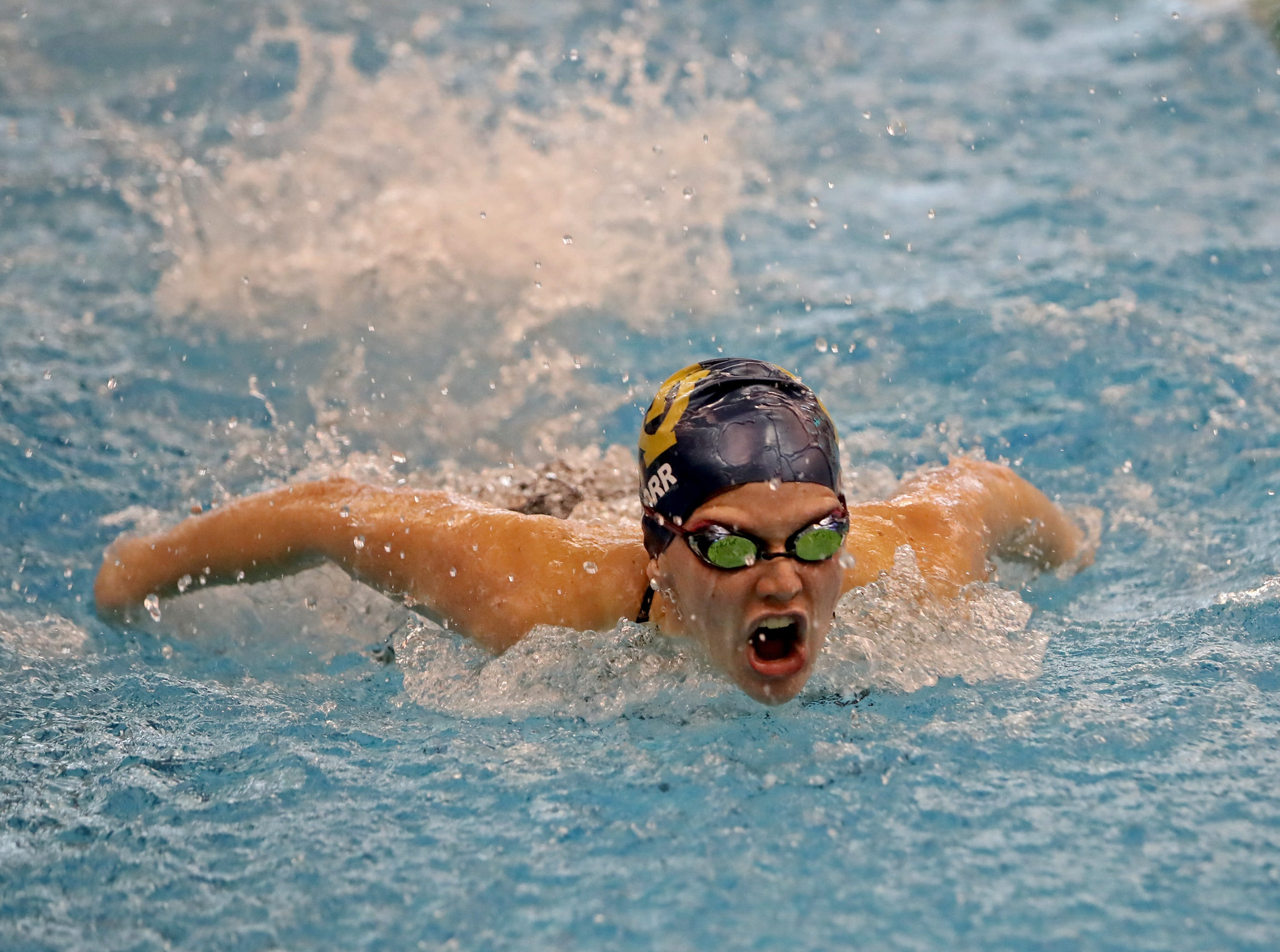 Megan Dorr from Walnut Hills wins her preliminary race in the girls 100-yard butterfly at the SW Ohio Swim Classic at Mason.