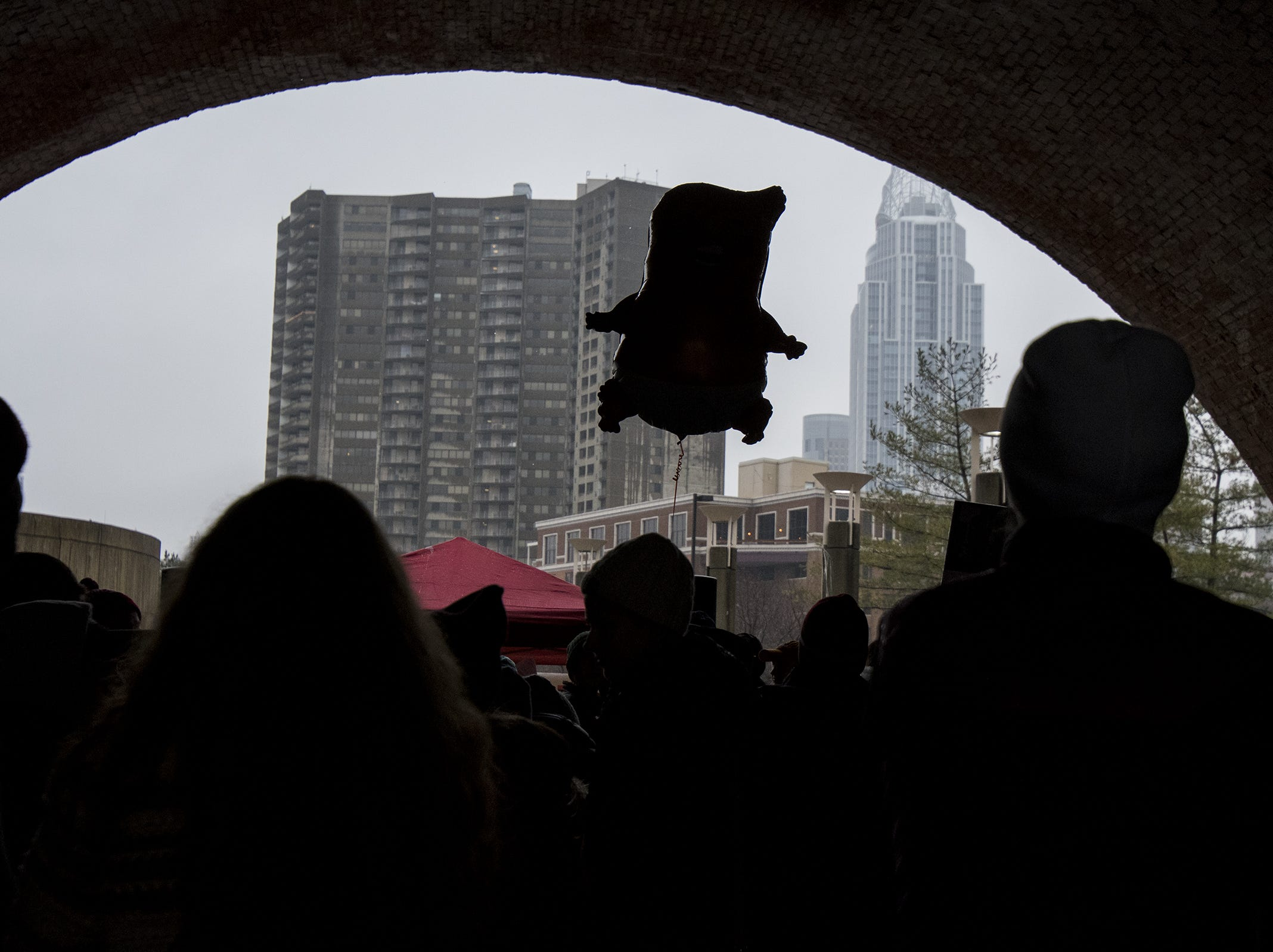 A Donald Trump-shaped balloon floats above demonstrators as they gather at Sawyer Point Park for the 2019 Women's March organized by the Cincinnati chapters of Socialist Alternative, Democratic Socialists of America and the International Socialist Organization Saturday, January 19, 2019 in Cincinnati, Ohio.