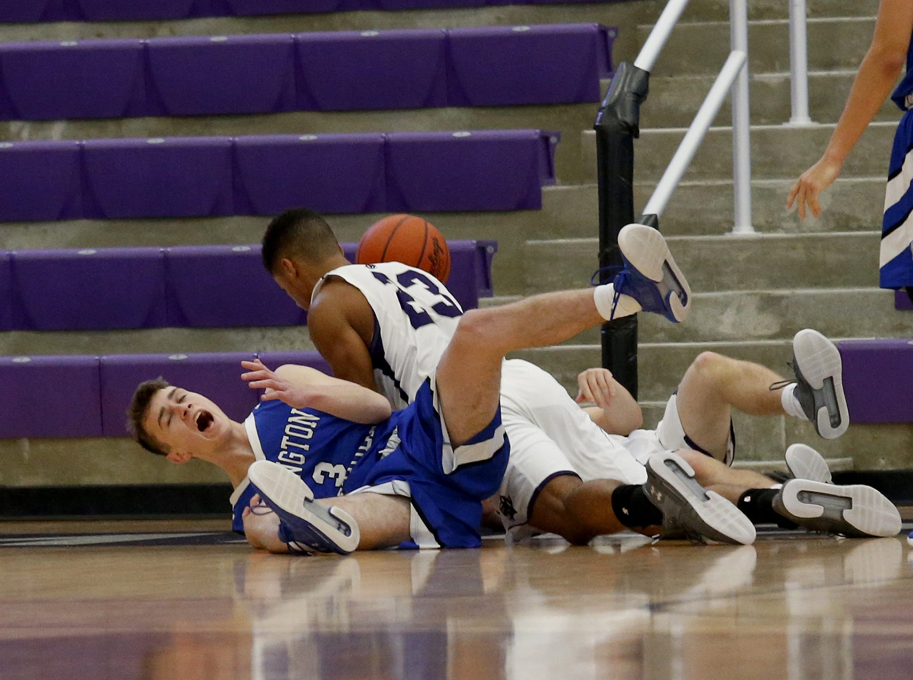 Several players, including Covington Catholic guard Mick Davin (3) and Elder forward Bryston Merz (23) hit the floor during the Midwest King Classic at Jerry Lucas Court in Wade E. Miller Arena in Middletown Saturday, Jan. 19, 2019.