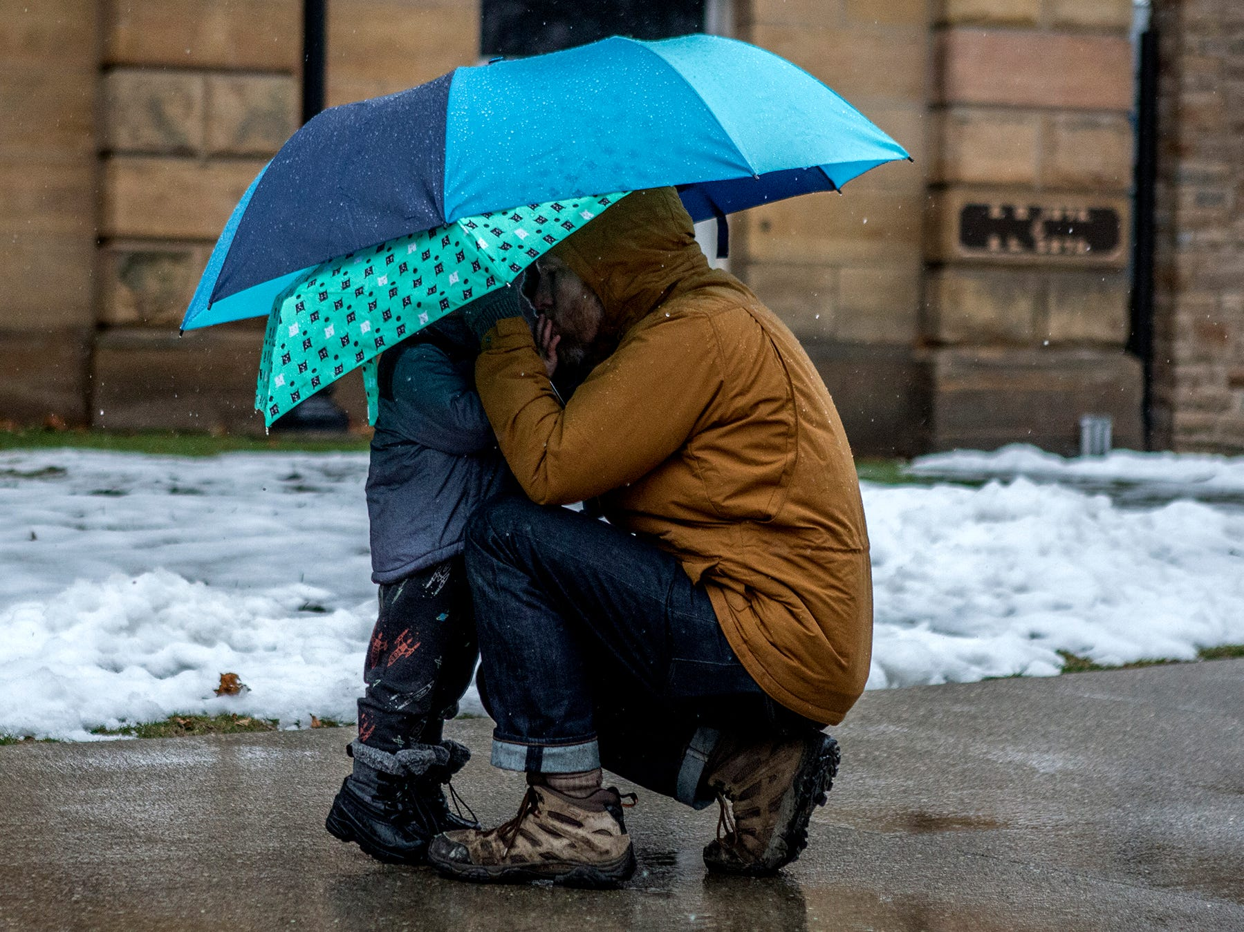Trent Beers speaks with his son, Arbor, 2, under the safety of an umbrella before the start of the Women's March in Newark Saturday afternoon.