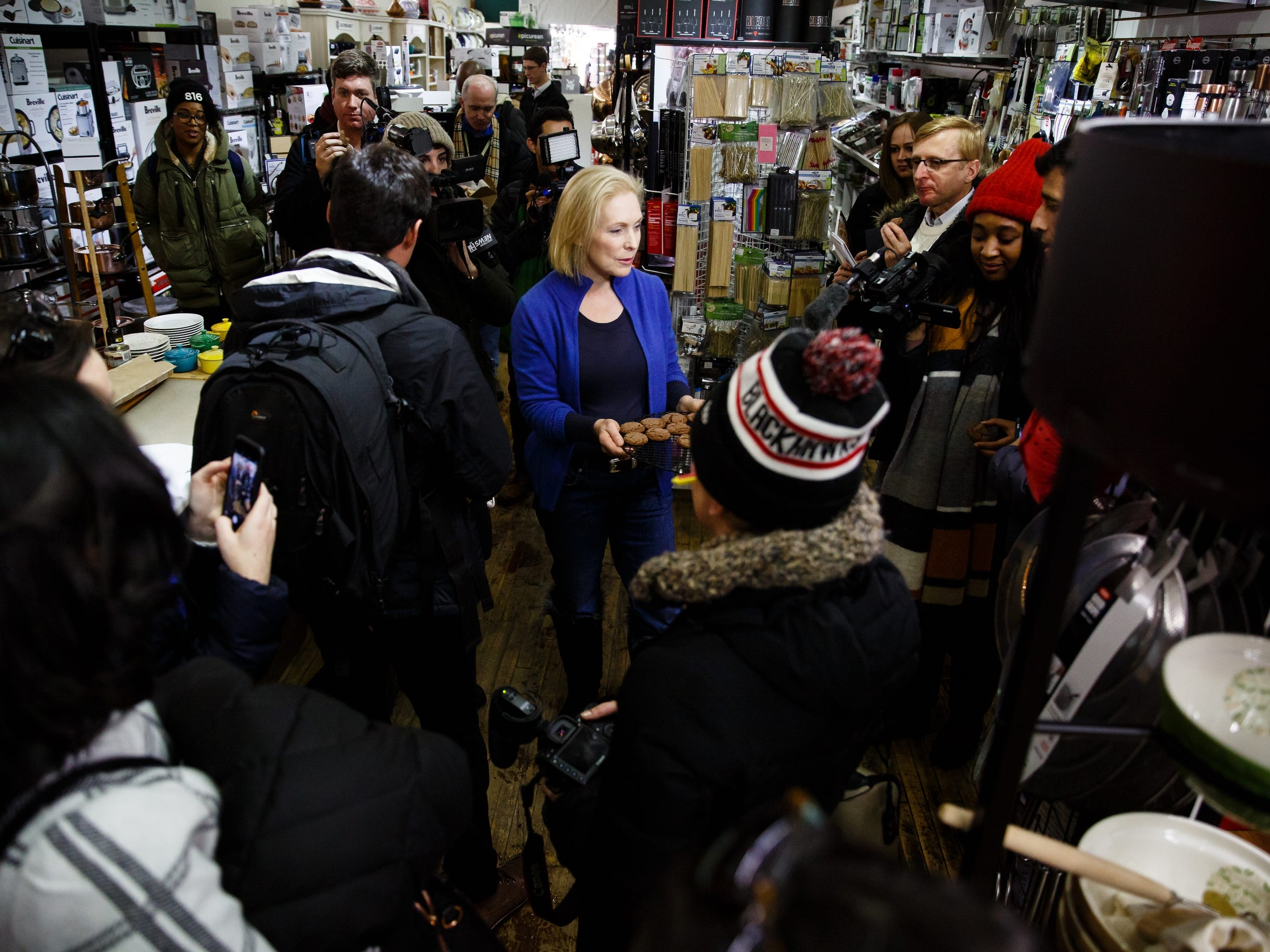 After baking cookies at Kitchen Collage, Sen. Kirsten Gillibrand of New York hands a few pre-made ones out to members of the press following her walking tour of the East Village on Saturday, Jan. 19, 2019, in Des Moines.