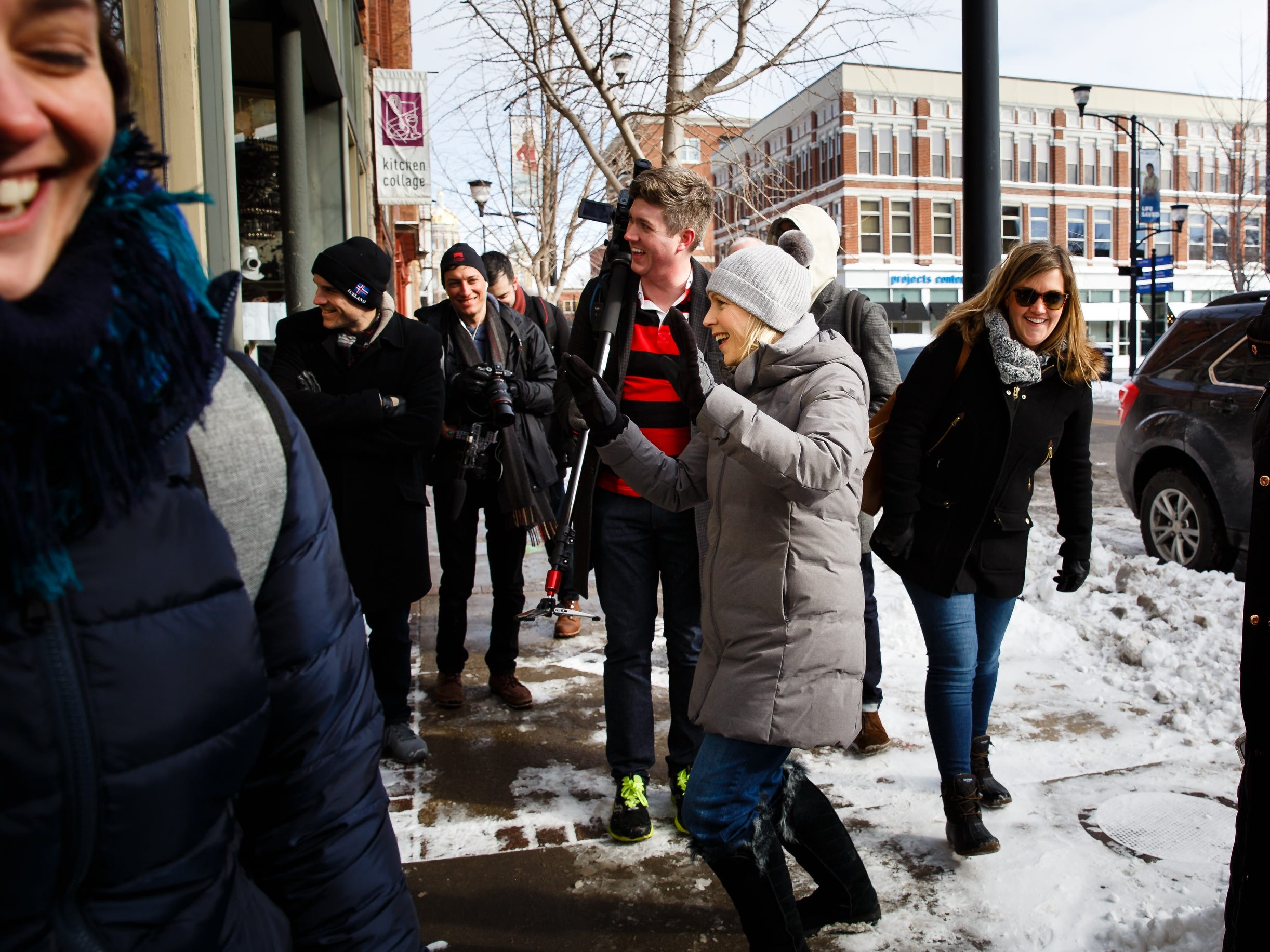 Sen. Kirsten Gillibrand of New York waves to patrons dining in the Continental during a walking tour of the East Village on Saturday, Jan. 19, 2019, in Des Moines.