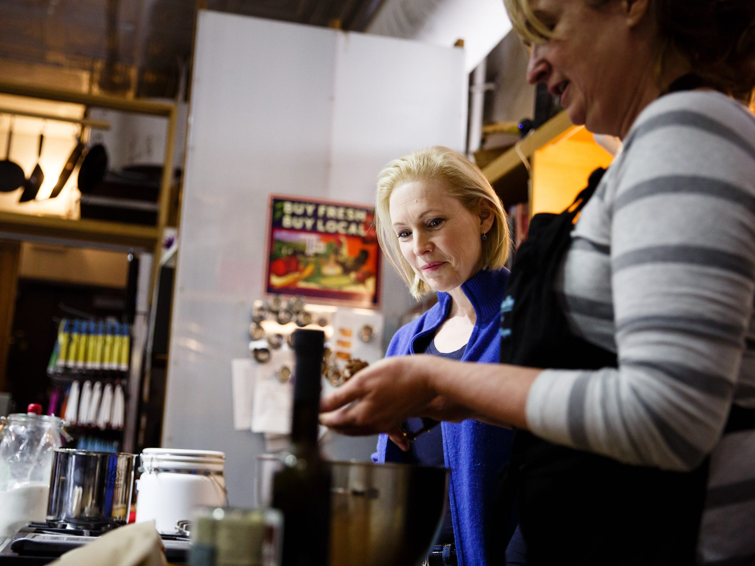 During a walking tour of the East Village, Sen. Kirsten Gillibrand of New York stops at Kitchen Collage and helps Jill Means bake a batch of chocolate cookies on Saturday, Jan. 19, 2019, in Des Moines.